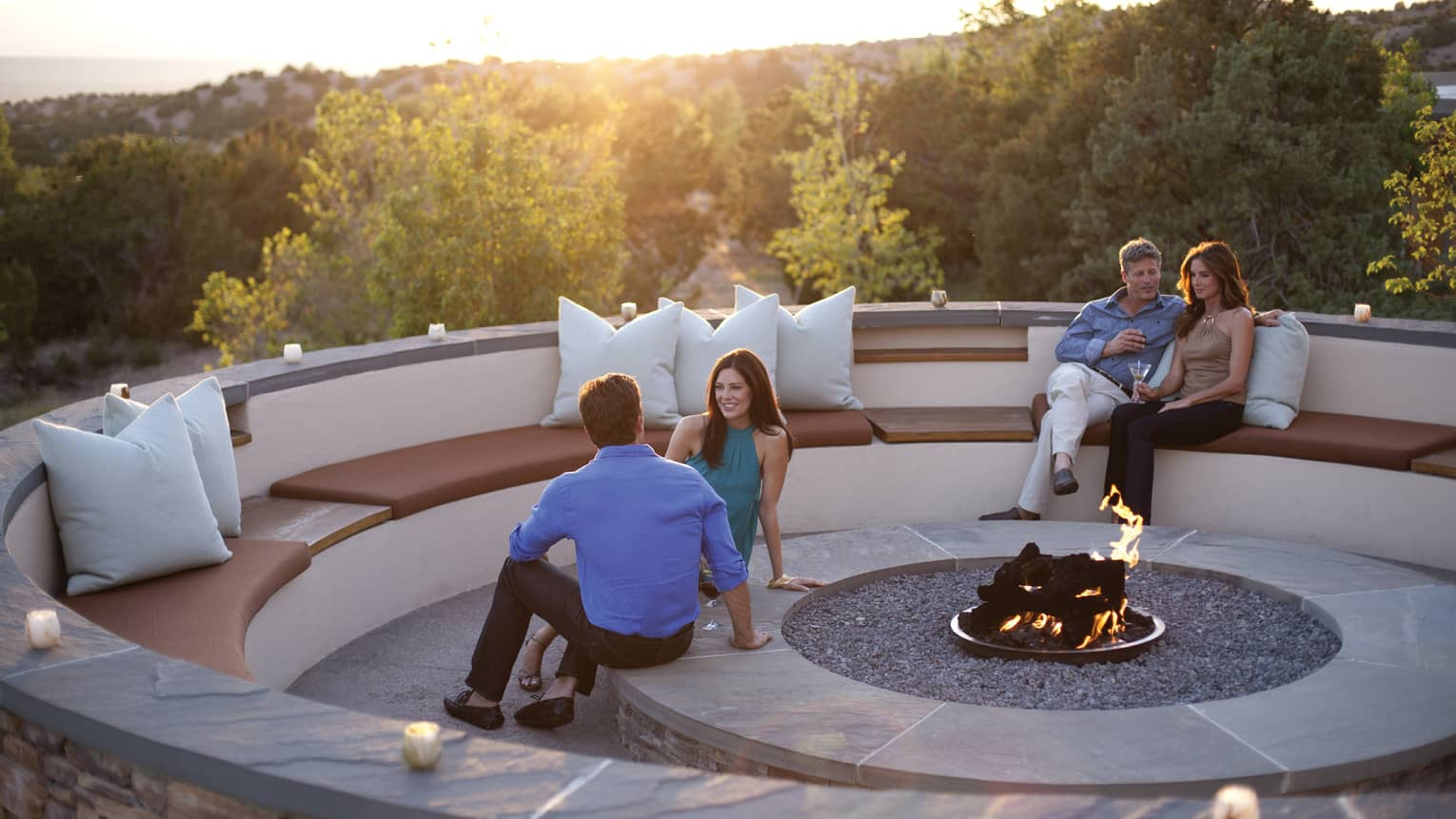 Couples sit within round, stone patio benches, modern outdoor fireplace