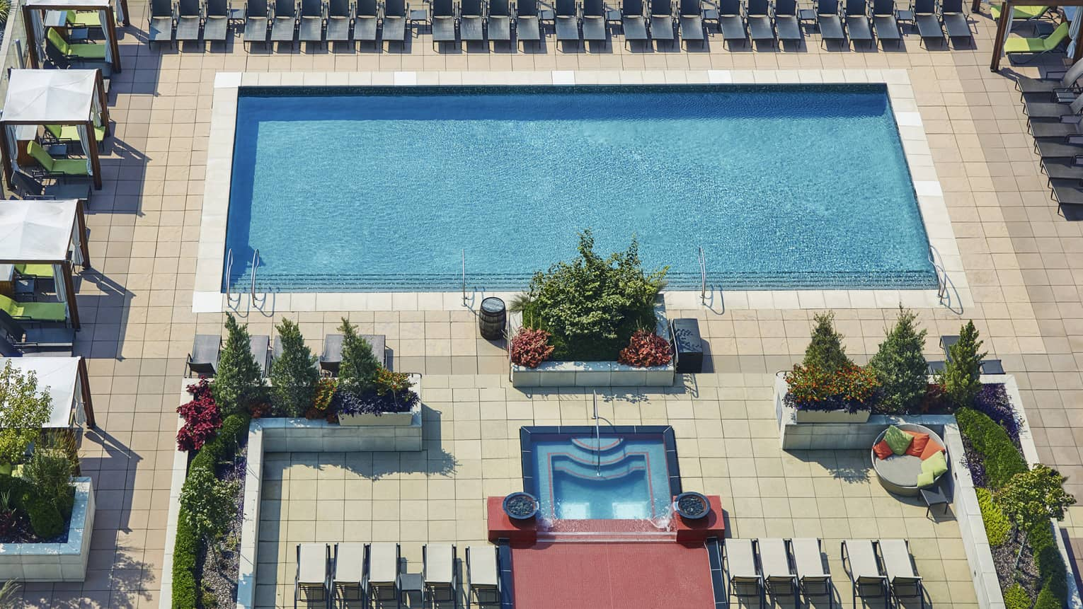 Aerial view of rooftop outdoor swimming pool and rows of patio chairs, cabanas