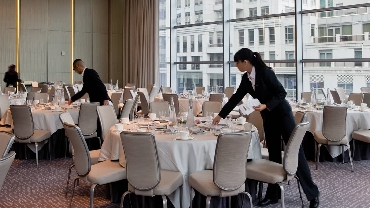 Hotel staff set round banquet tables in meeting room