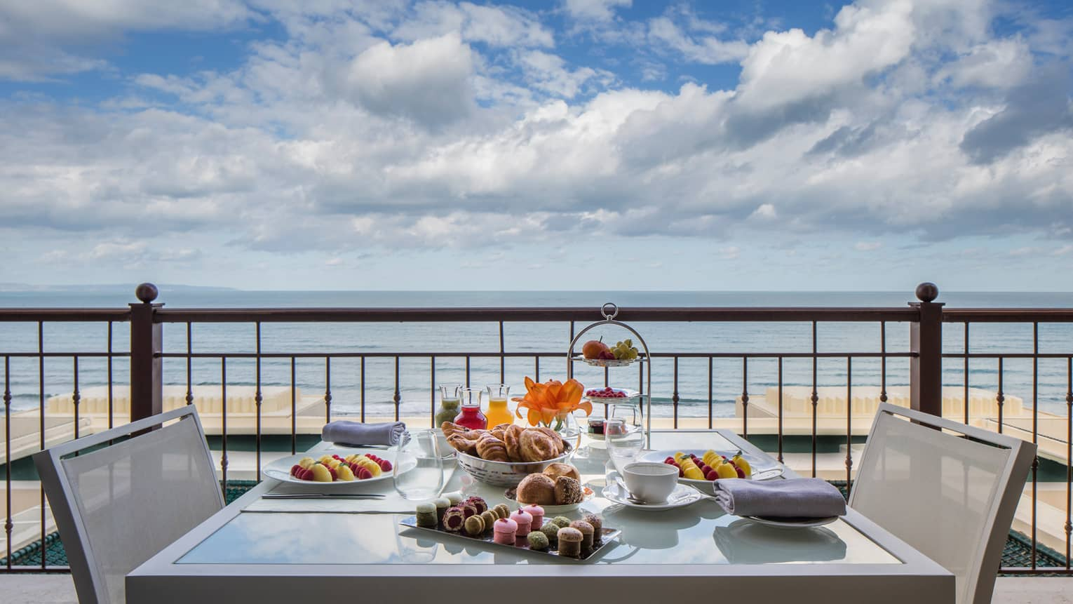 Balcony table set with fresh pastries, cakes, fruits, sea in background