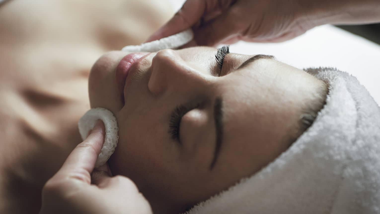 A detail of hands rubbing a sponge on a woman's face as she lies on a massage table with her eyes closed and hair wrapped up in a white towel