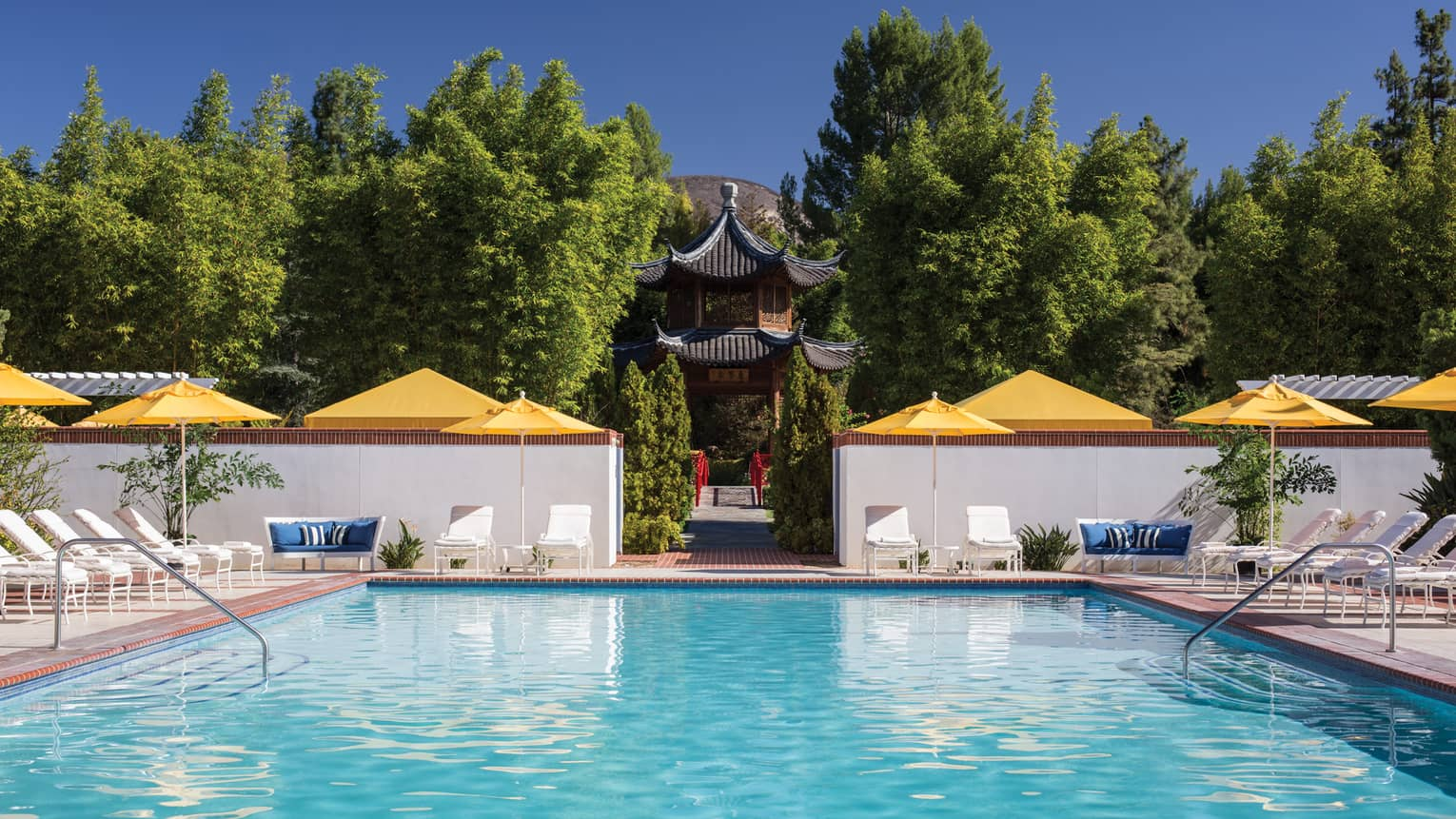 Outdoor swimming pool lined with lounge chairs, yellow umbrellas, path to temple, trees