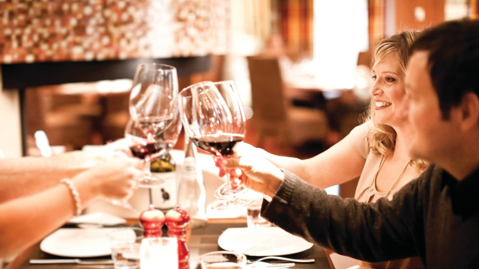 Diners toast with wine glasses at dining table, man and woman smile