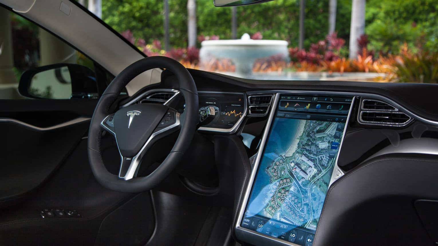 Close-up of Tesla car wheel, dashboard with touchscreen