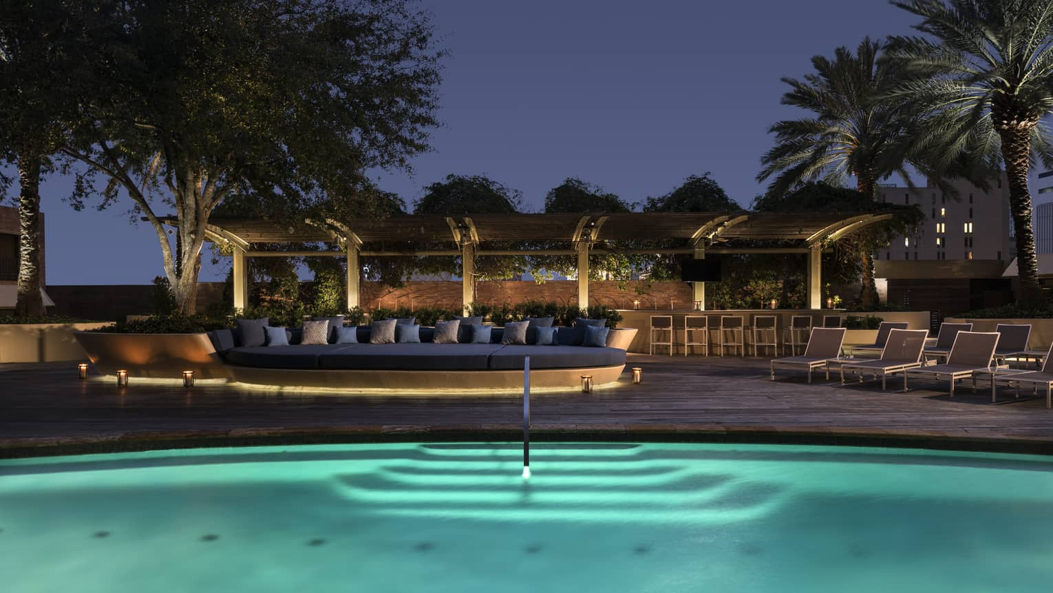 Outdoor swimming pool with lights and patio with large banquette at night