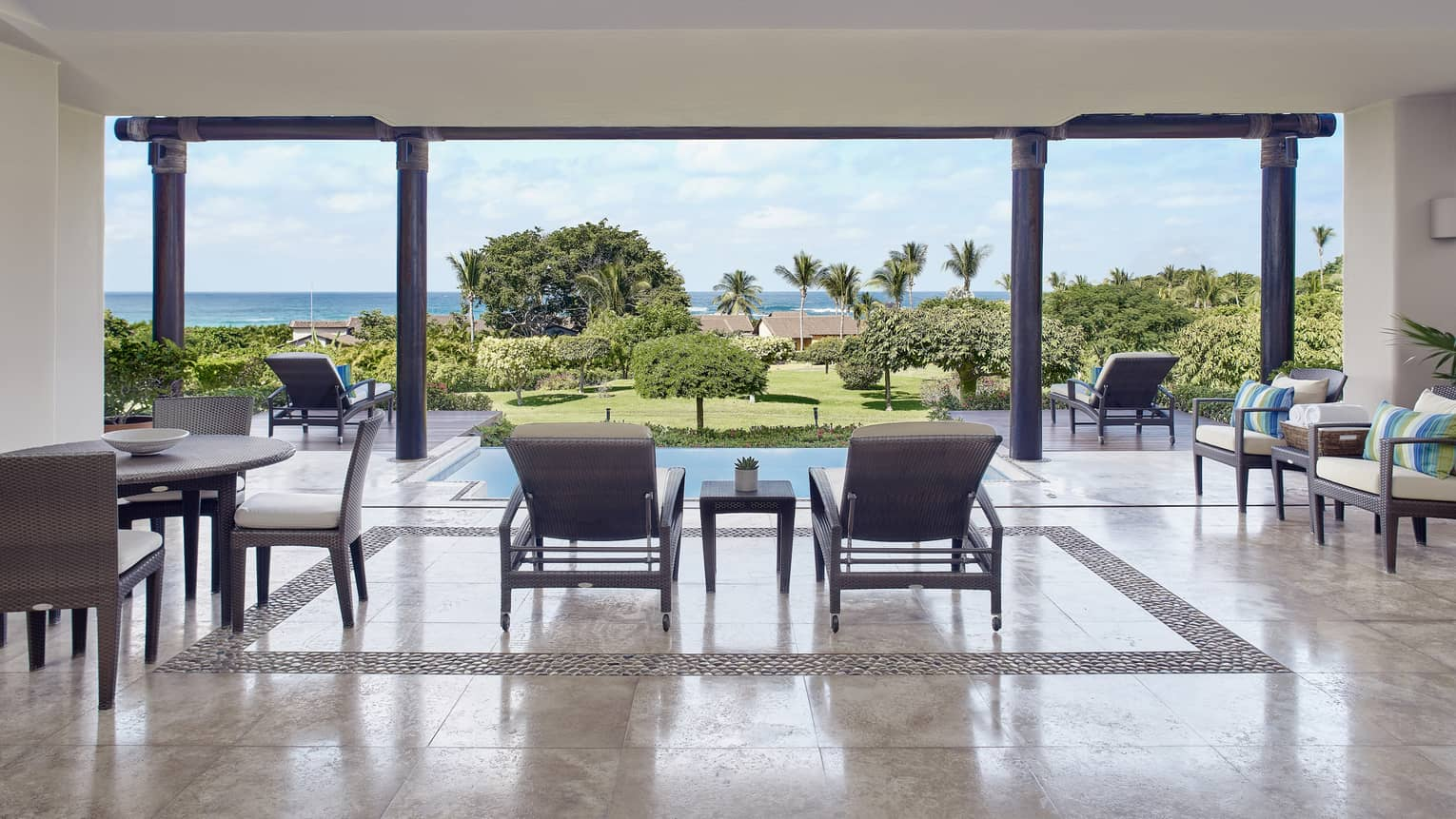 Terrace with dining table and lounge chairs, looking out to private pool and ocean in the distance