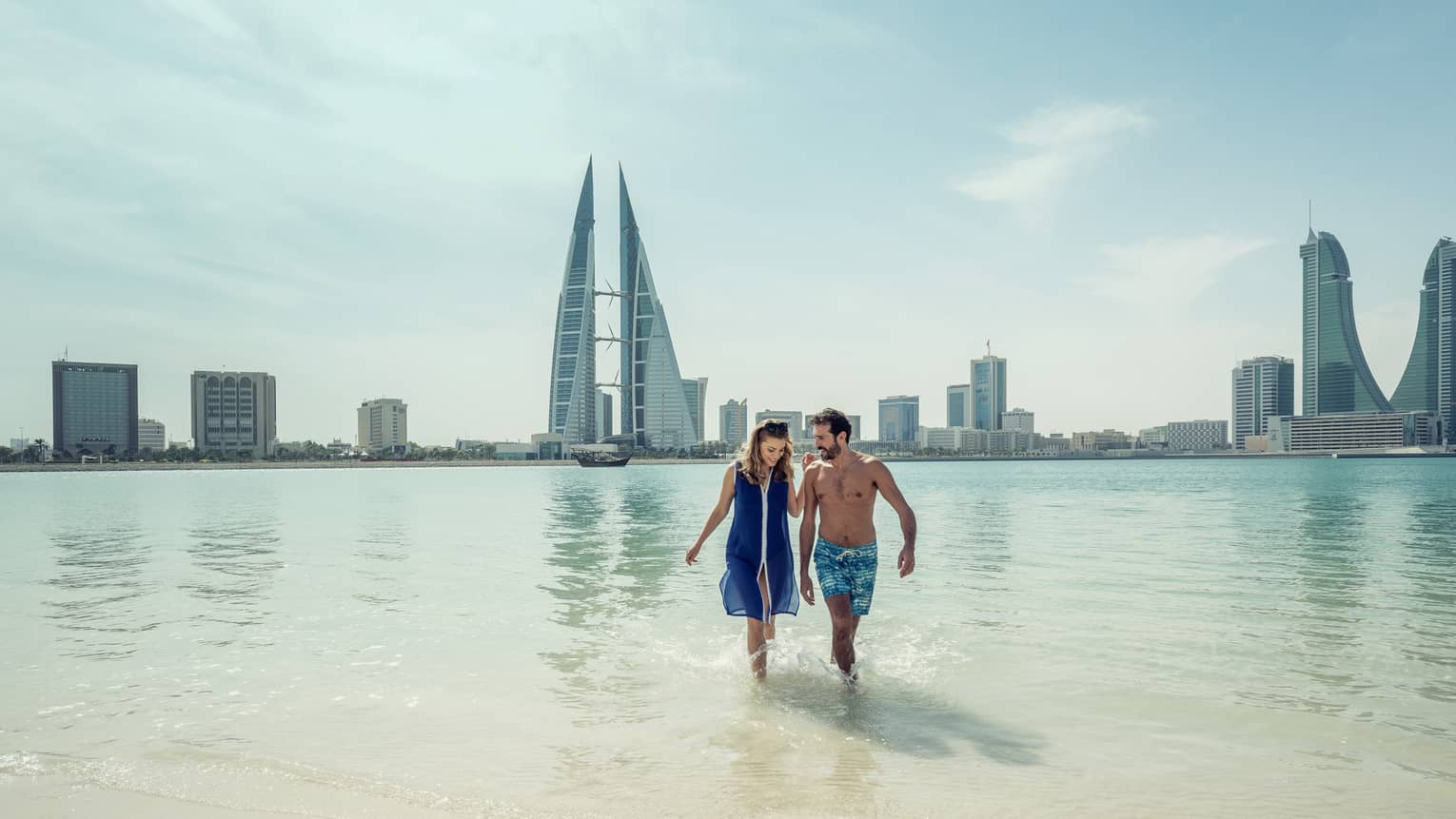 A man and woman run arm in arm through the shallow ocean water with Bahrain Bay skyscrapers in the background