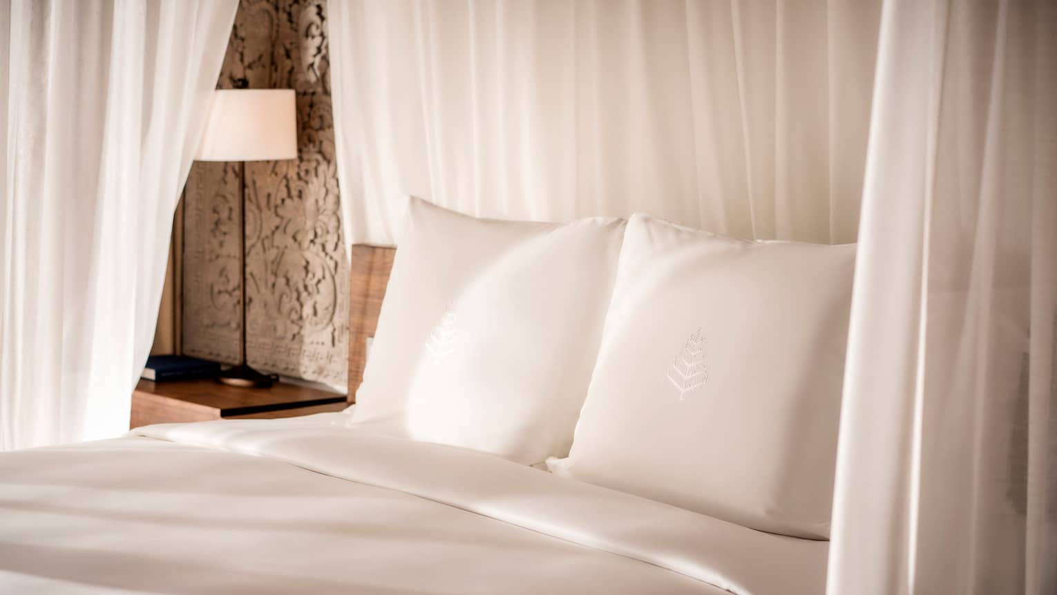 Close-up of bed headboard, white pillows with Four Seasons logo embroidered, crisp white linens, white curtains