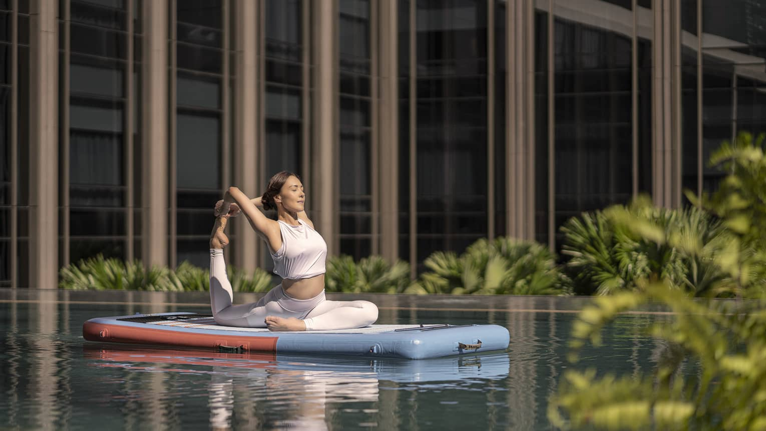 Woman doing a yoga pose on a floating paddle board in hotel pool
