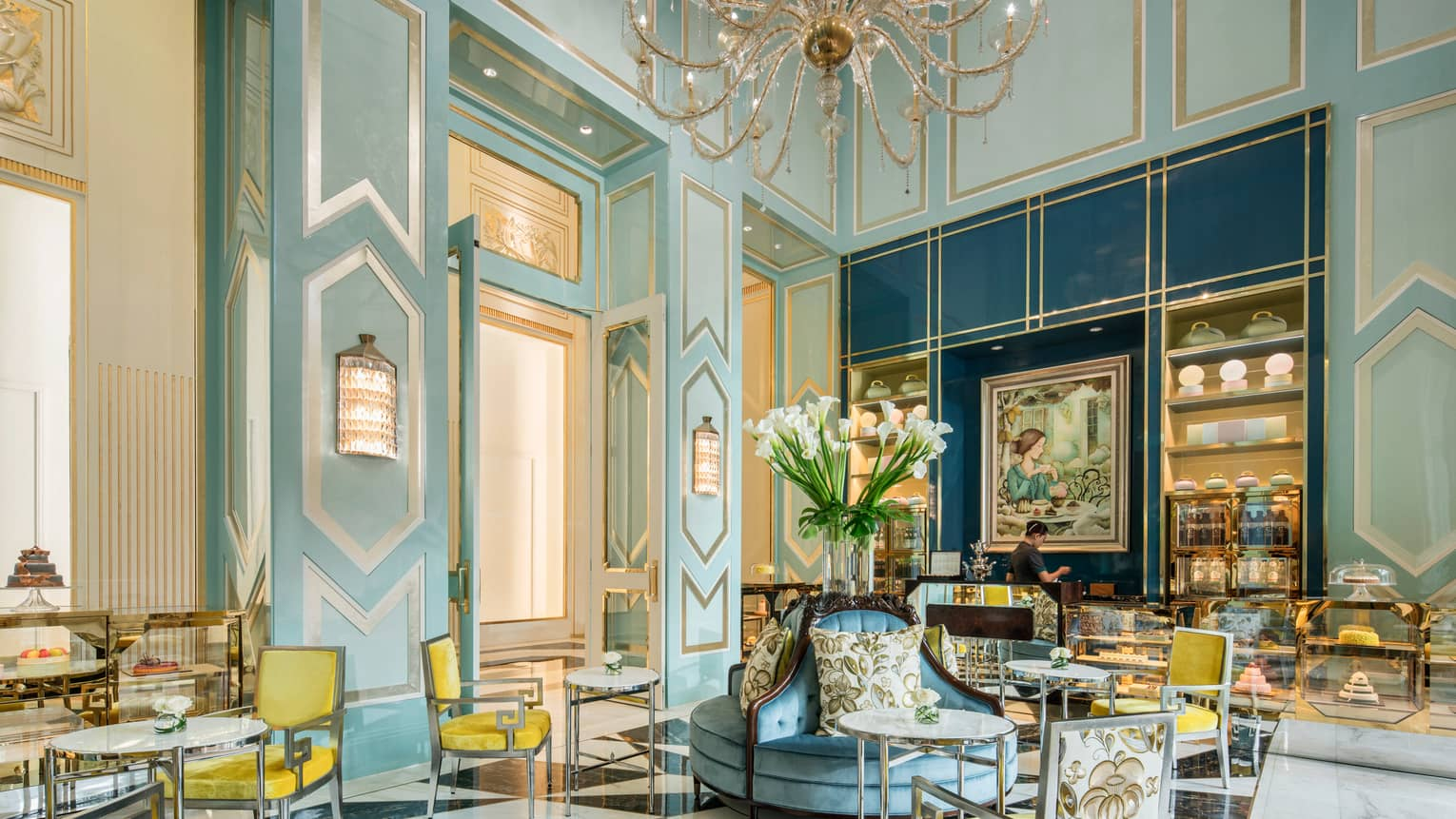 Bright La Patisserie cafe with elegant blue decor, yellow chair, high ceilings, crystal chandelier