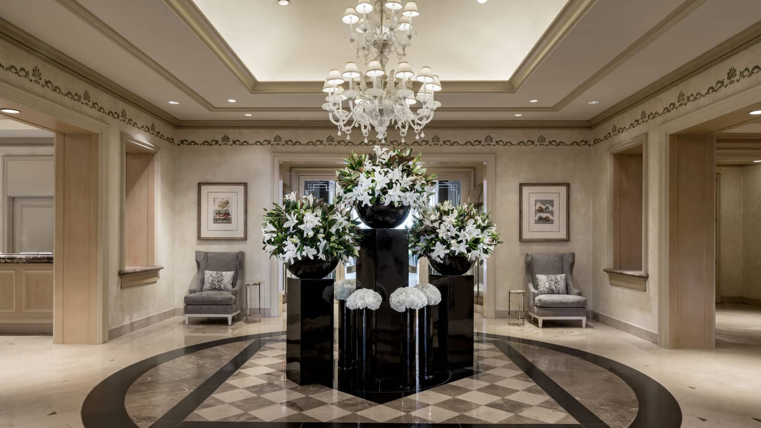 Large white floral displays on black tables under crystal chandelier in hotel lobby