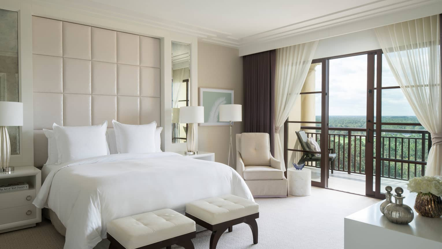 Grand Suite bed against white padded wall, bench, white armchair by windows with sheer curtains