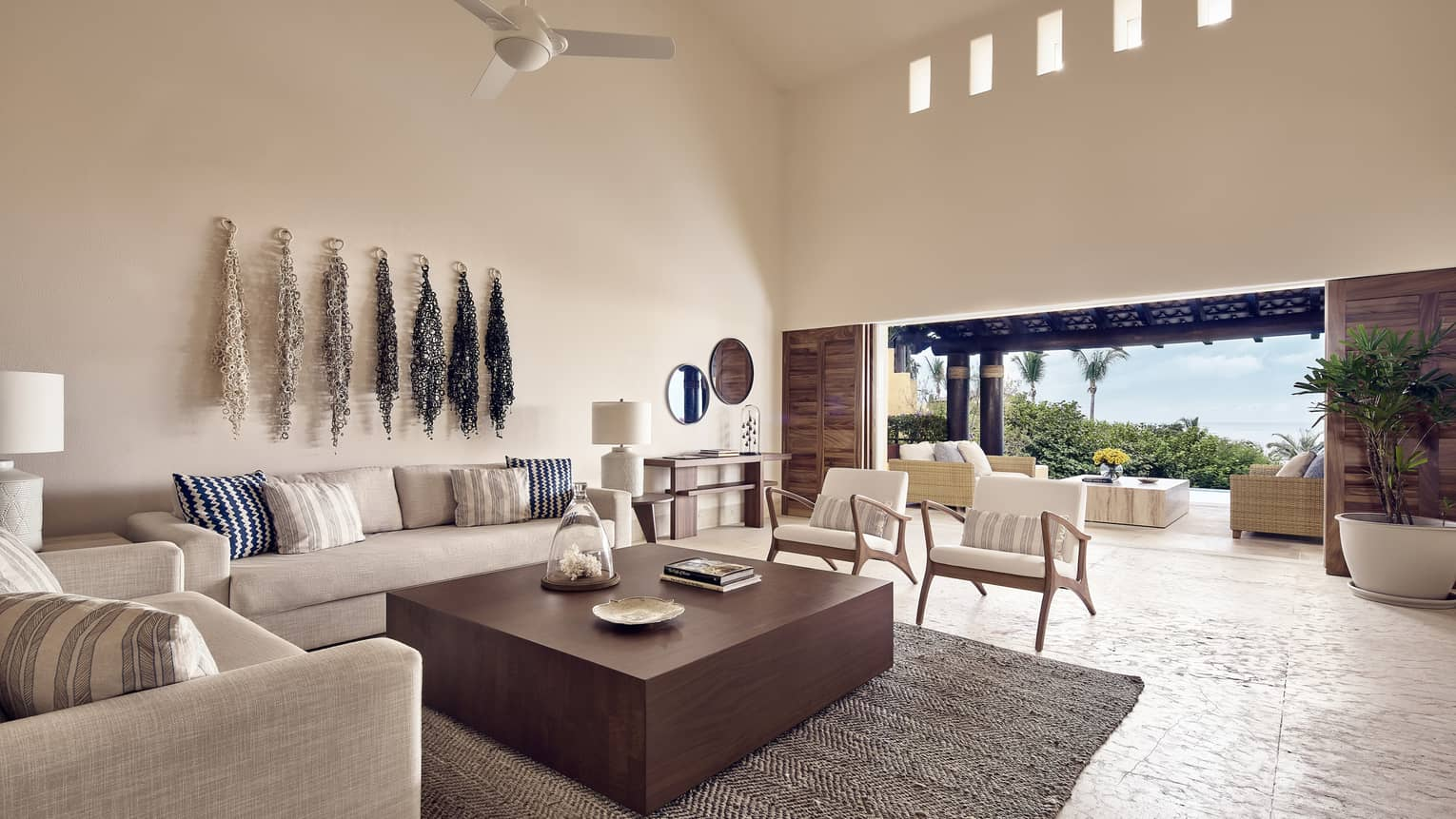 White linen sofas around large wood coffee table in bright living room, open patio wall