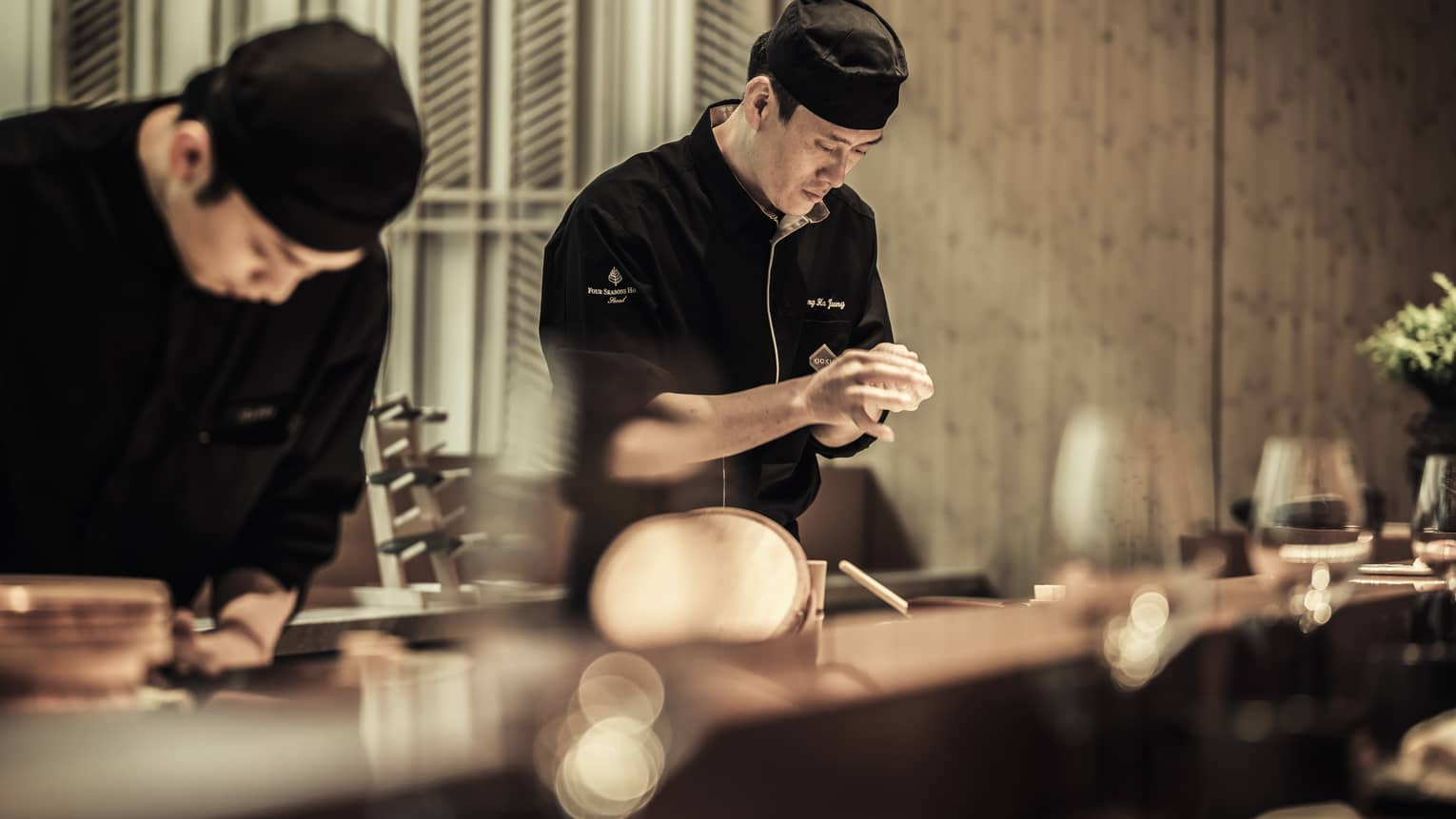 Chefs wearing black uniforms prepare dishes at Kioki sushi bar
