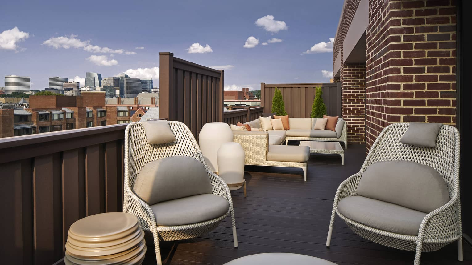 A large, outdoor terrace with cozy chairs and couches