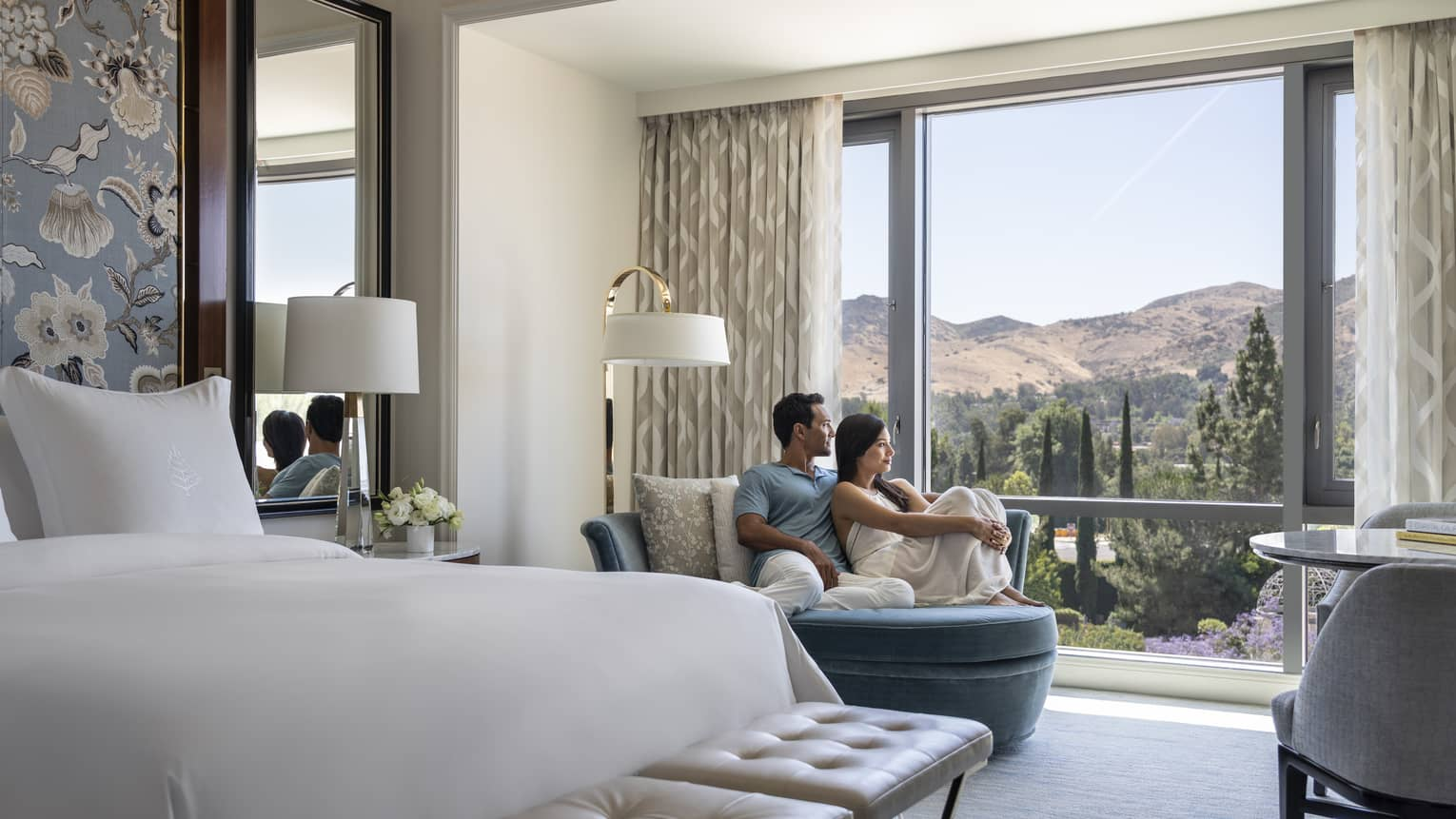 A couple lounging on a chair in their hotel room looking out at the mountains.