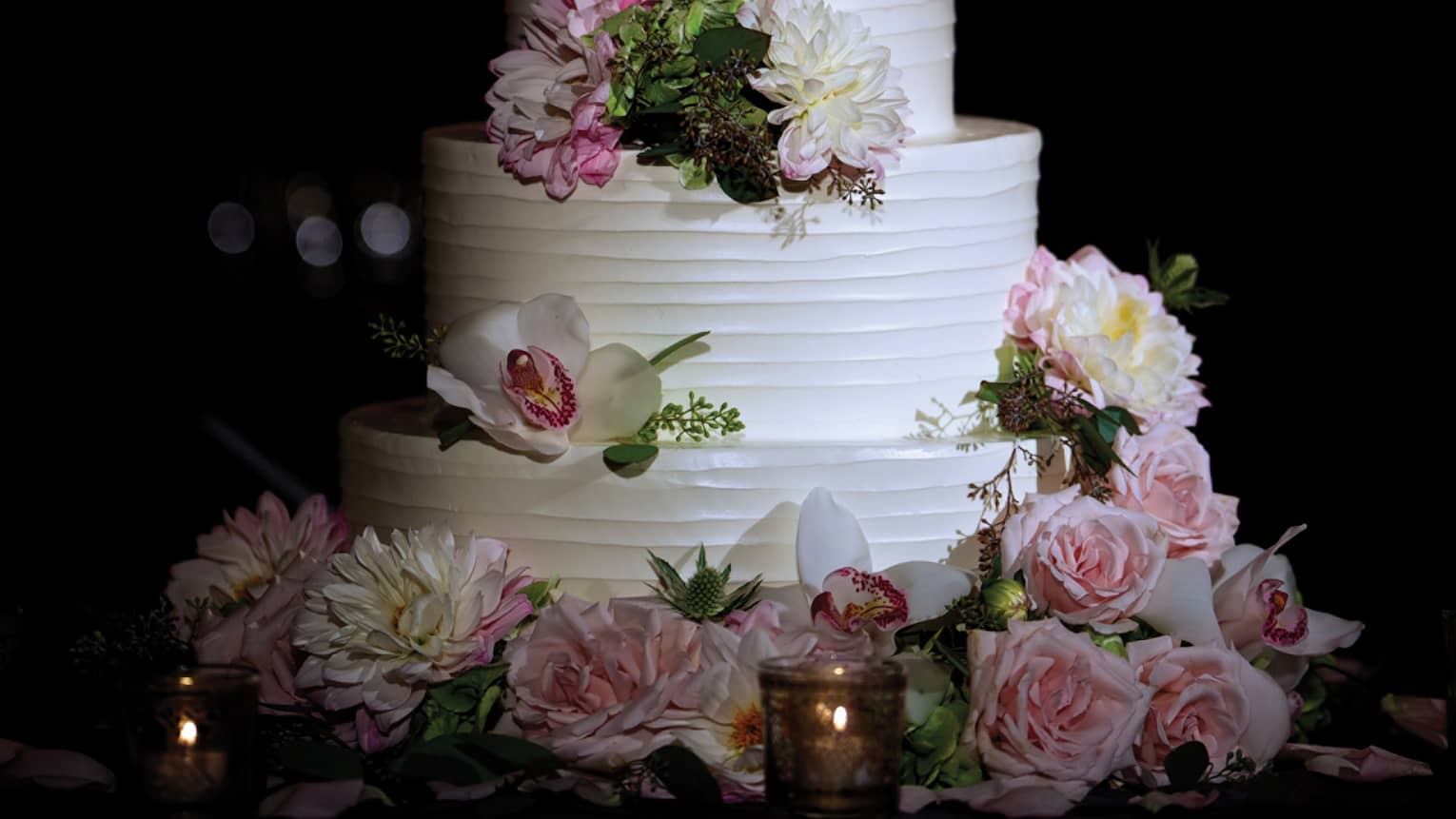 Close-up of white tiered wedding cake garnished with fresh pink flowers