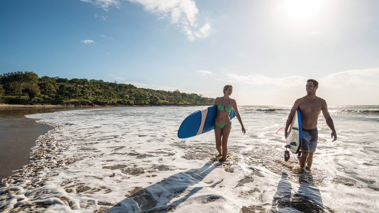 Man and woman in swimsuits walk on beach through surf holding surfboards