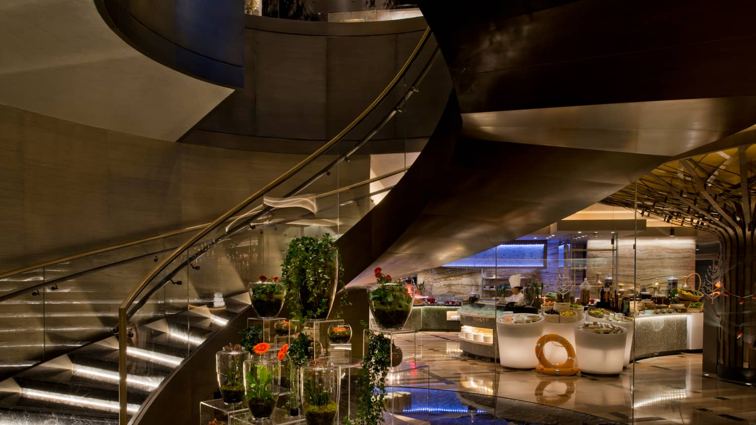 Floral display under spiral black marble staircase with glass railings at Bahrain Bay Kitchen