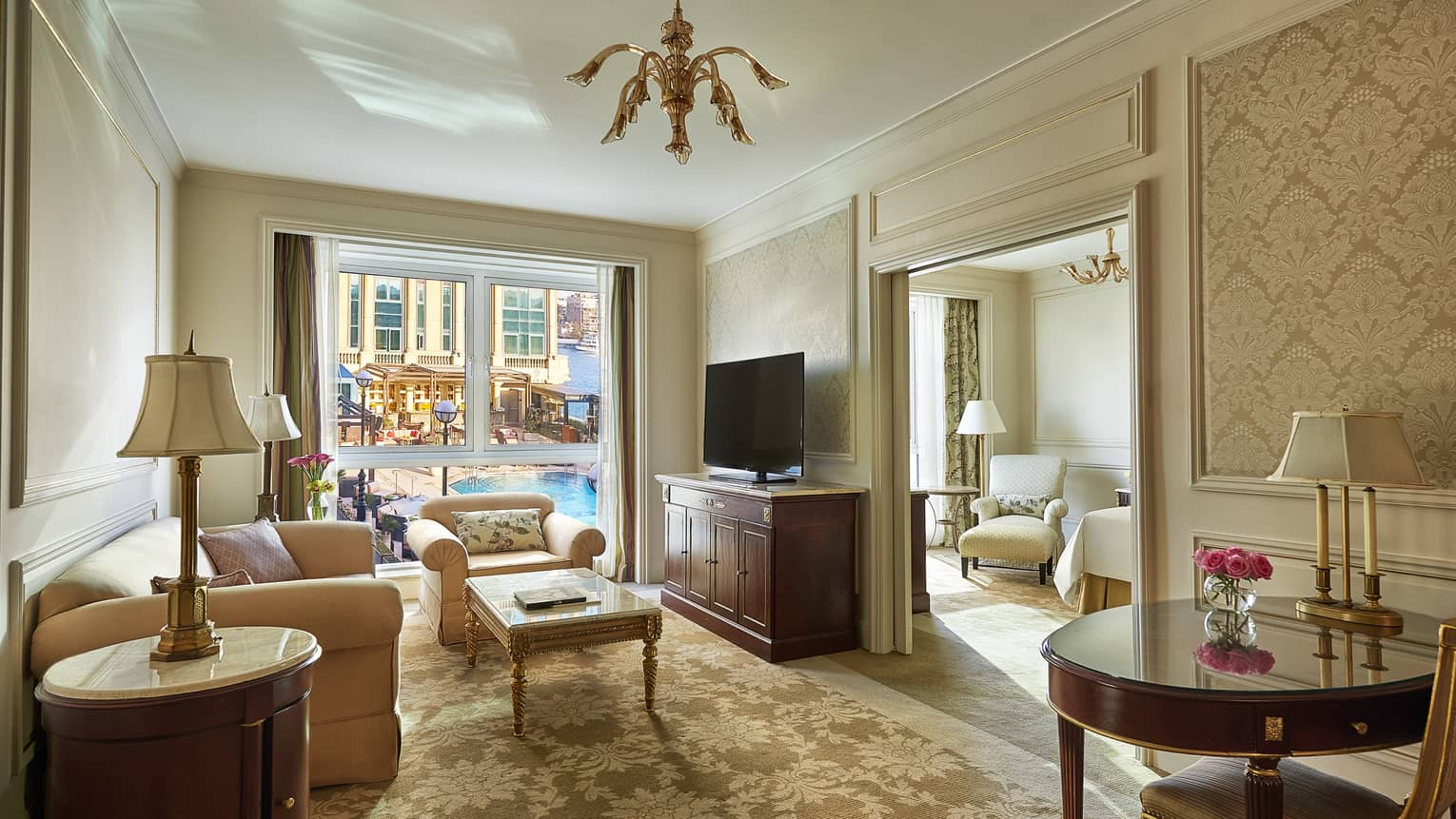 Four Seasons Executive Suite living room with plush sofa, armchairs, window overlooking patio, pool