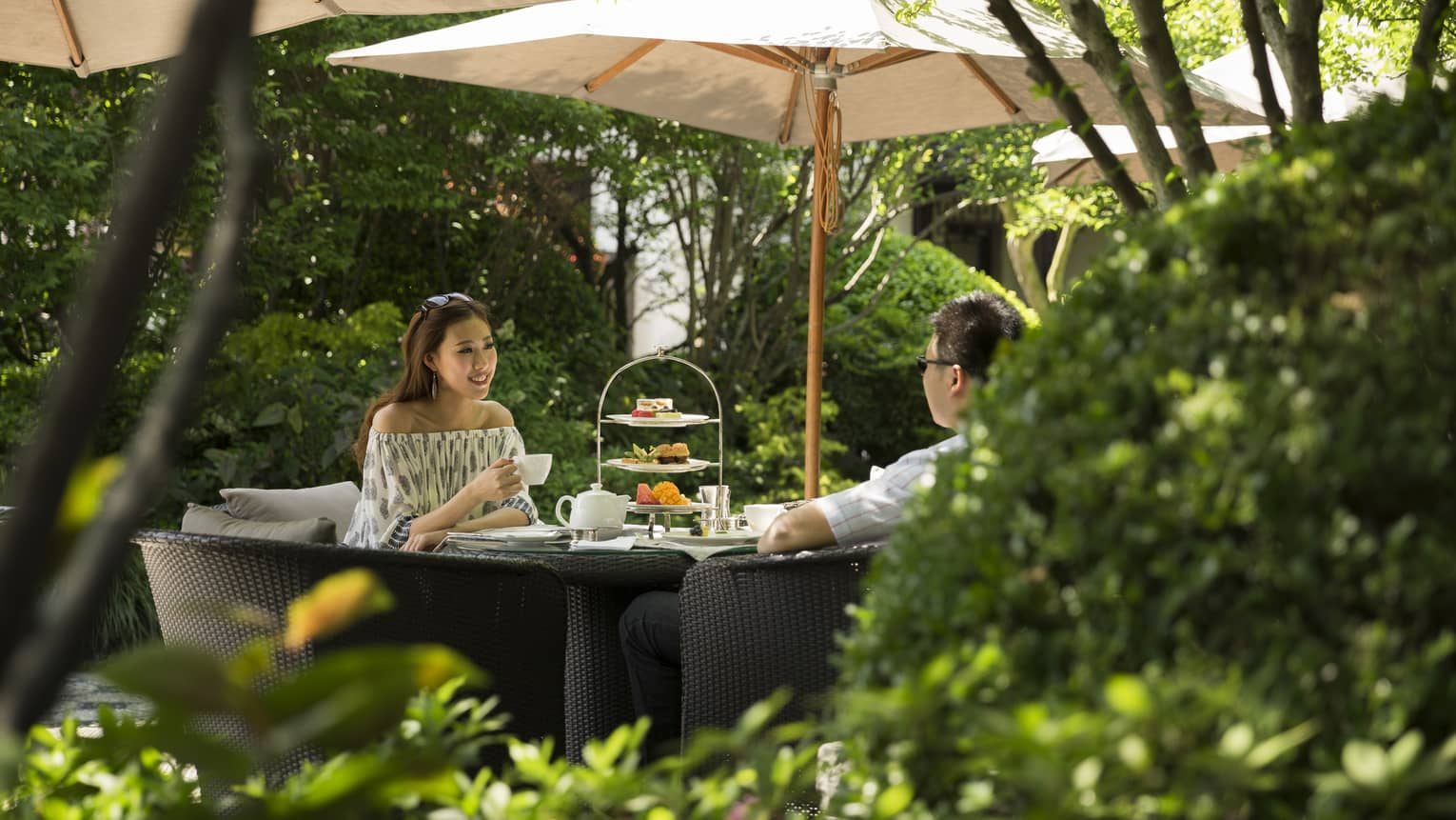 Woman and man drink tea near tray of sweets at table under shade of patio umbrella