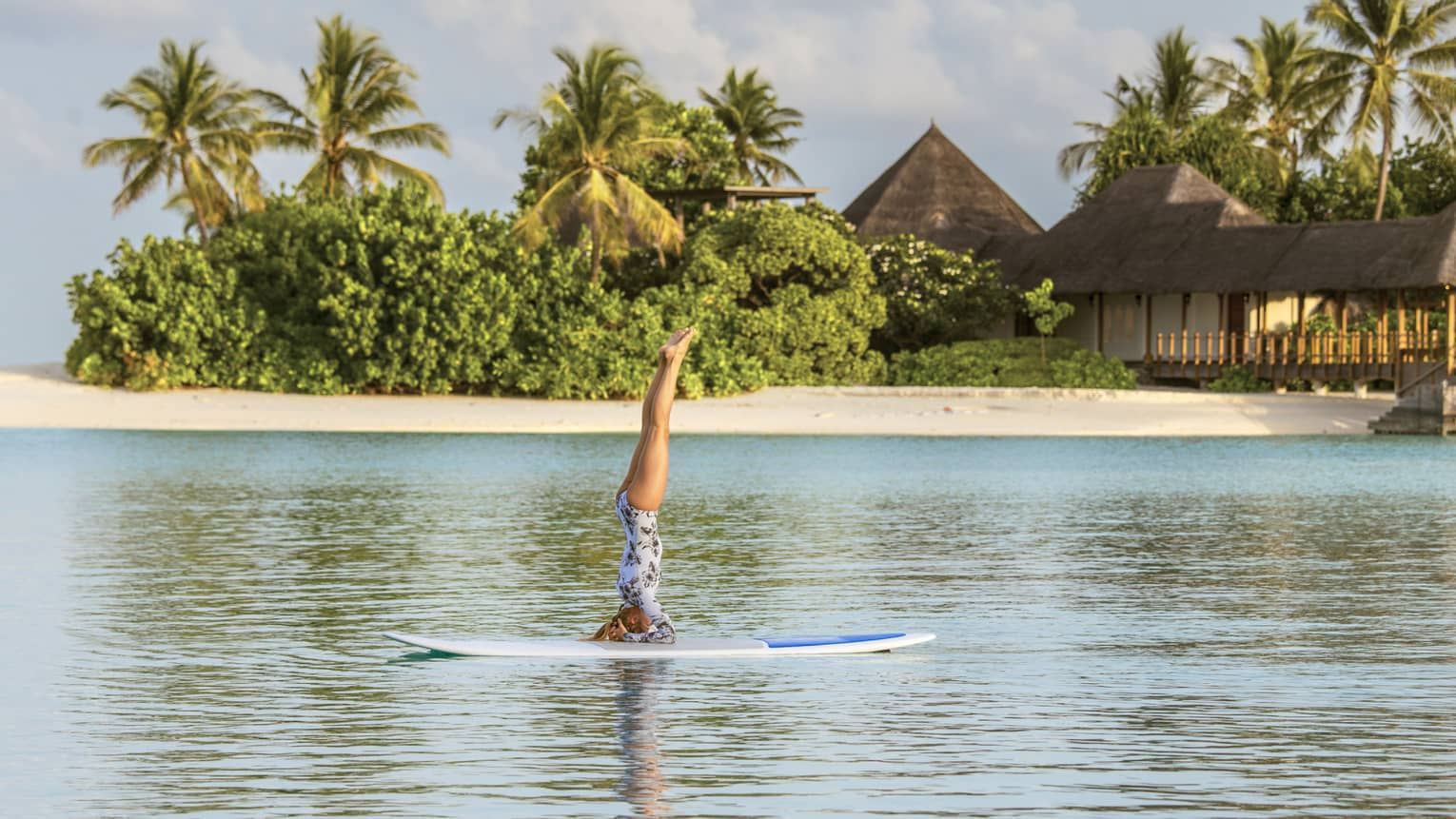 Woman balances on arms during stand-up paddleboard yoga session on Indian Ocean