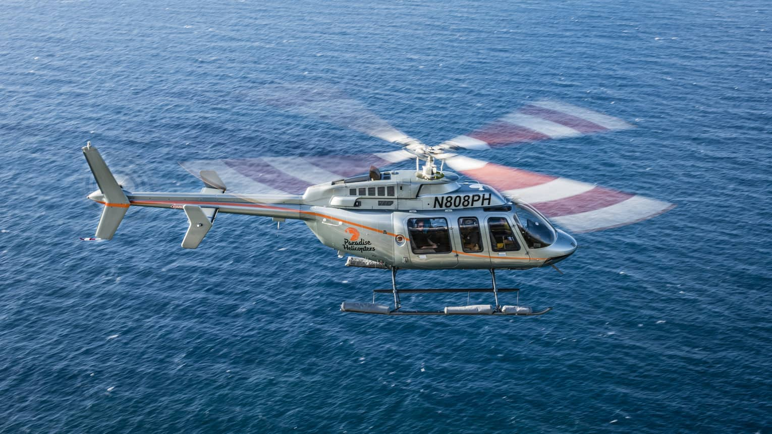 Helicopter flying over blue ocean