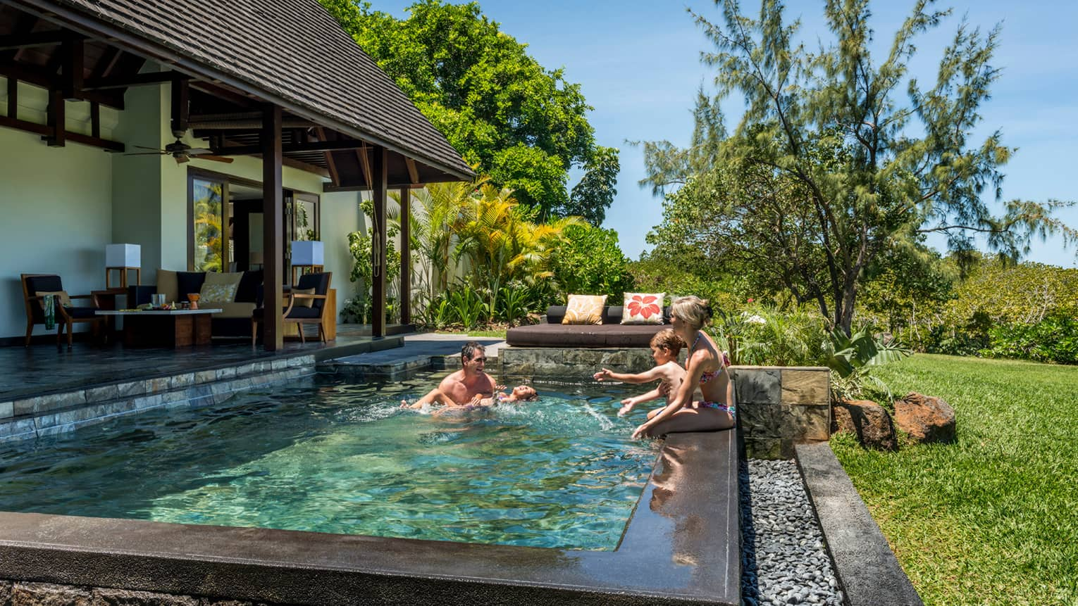 Couple, two children laugh, splash in sunny Garden Villa plunge swimming pool