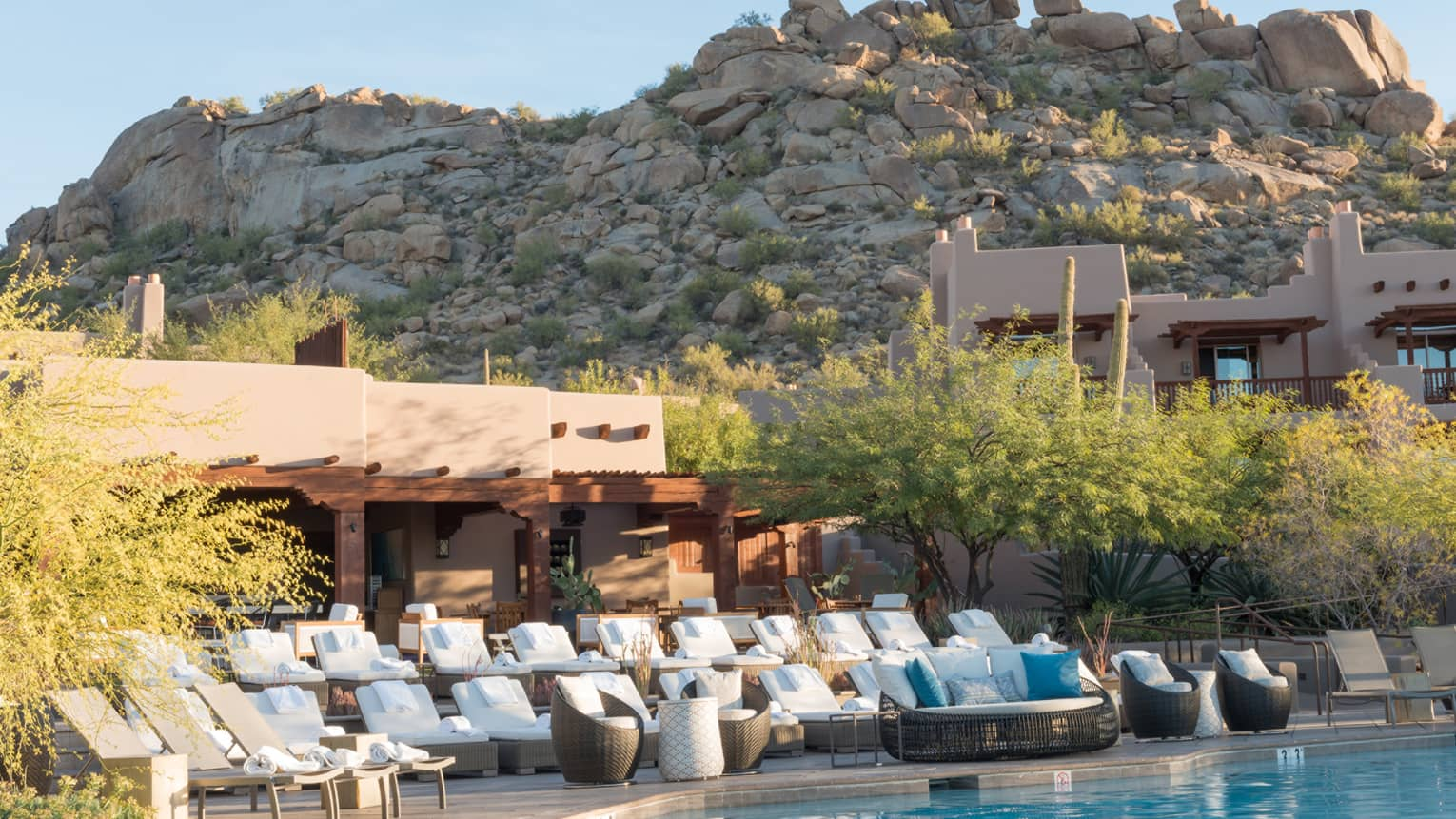 Rows of white lounge chairs on bi-level patio beside outdoor swimming pool under large desert rock face
