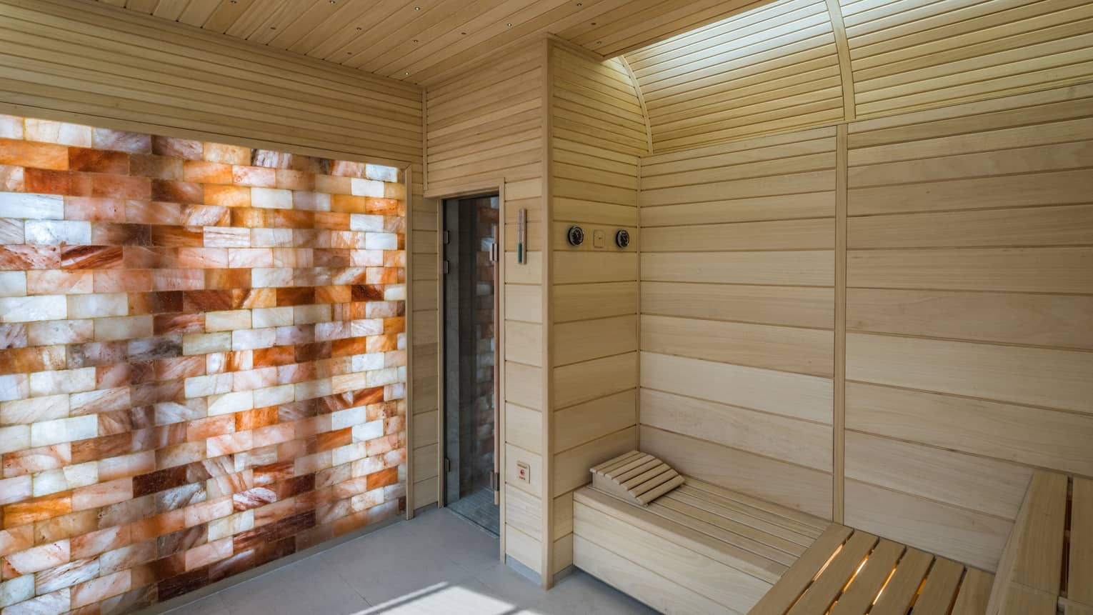 The Club wood sauna room with illuminated wall with wood, brick pattern