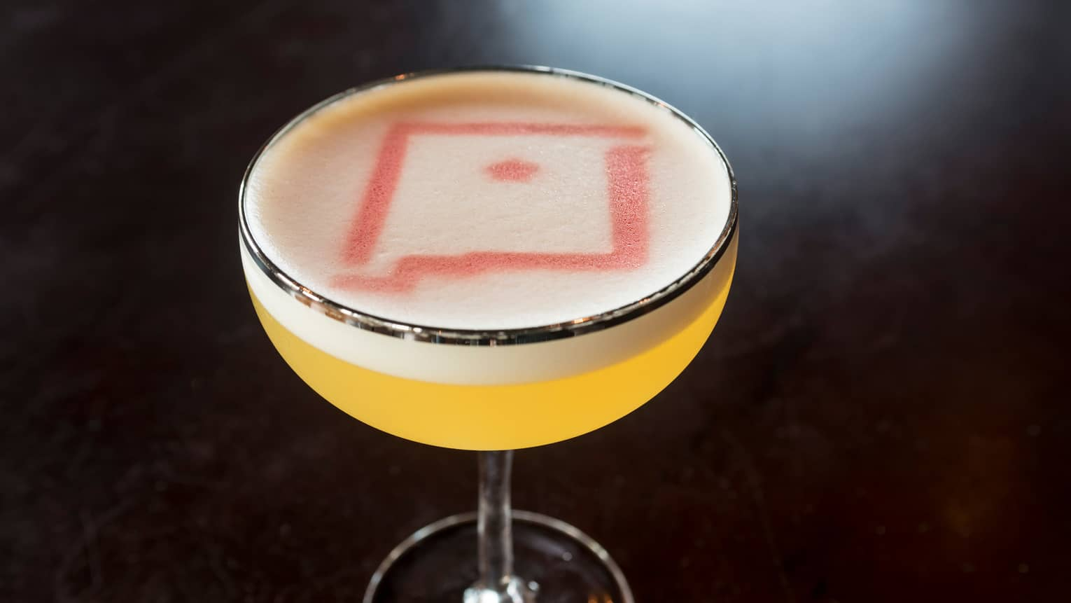 Yellow cocktail in glass topped with foam, red design