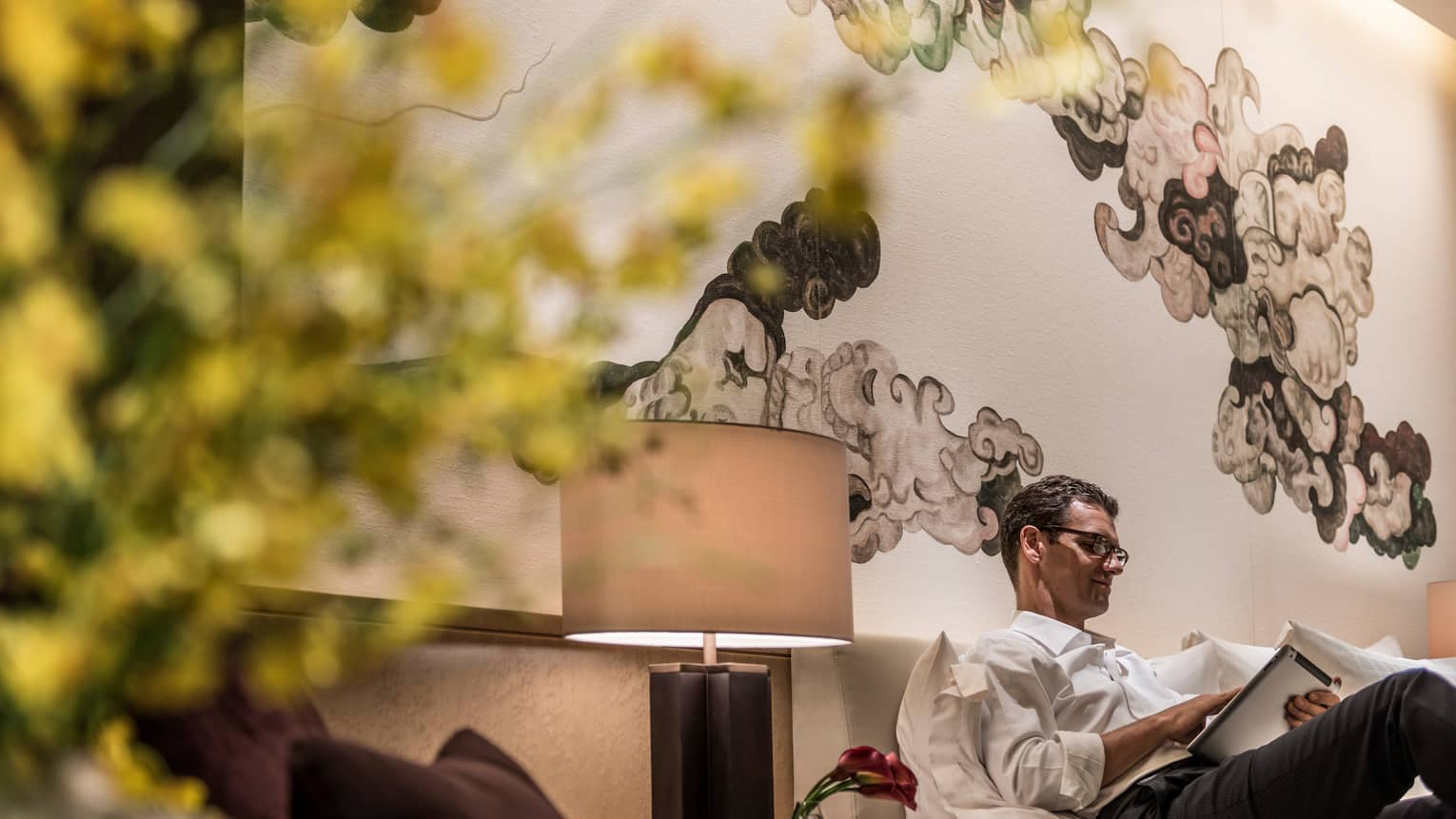 Man lounges, reads iPad on sofa next to lamp under black-and-white Chinese brushwork mural