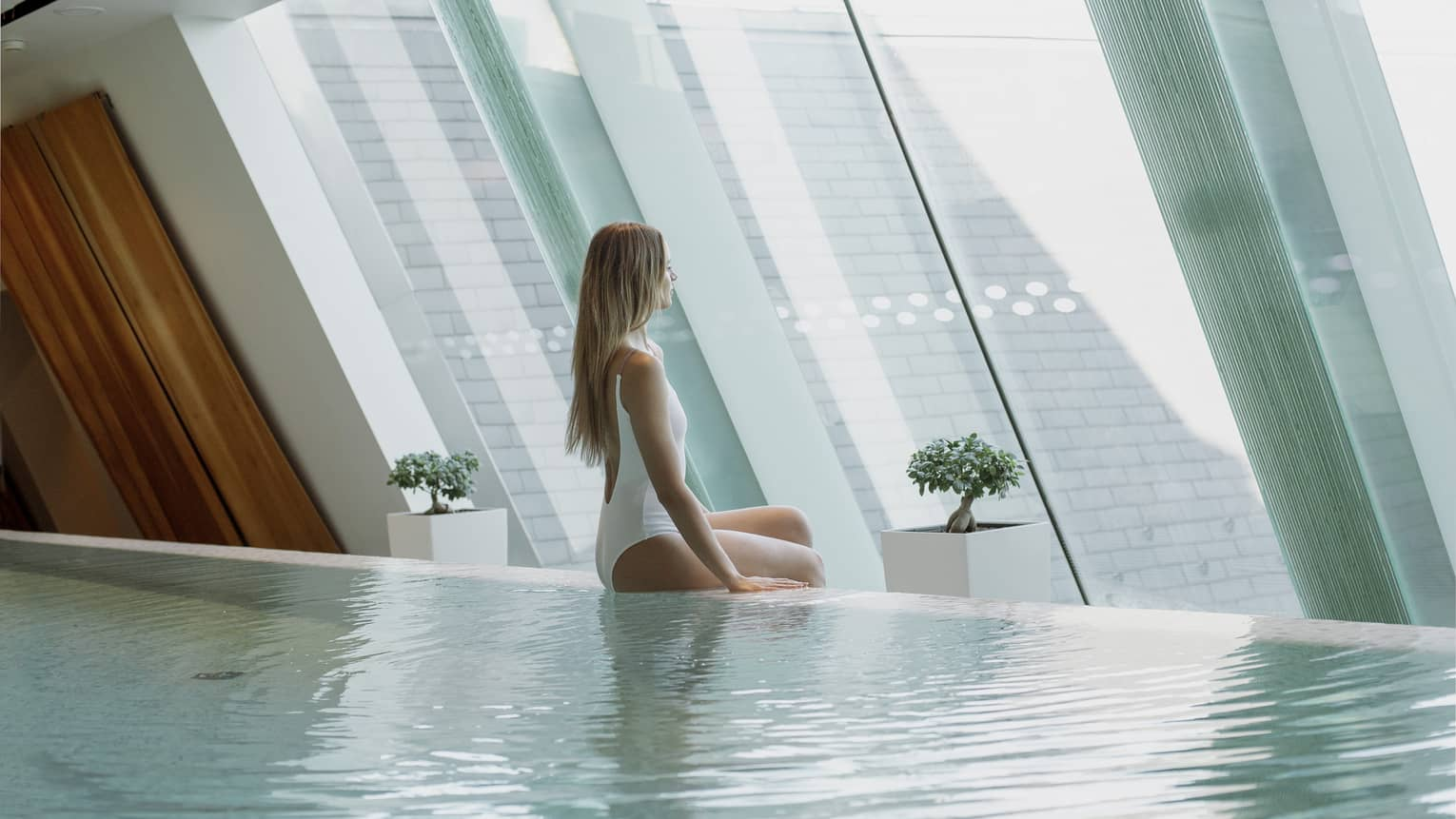 Woman wearing white swimsuit sits on edge of indoor swimming pool, looks out window