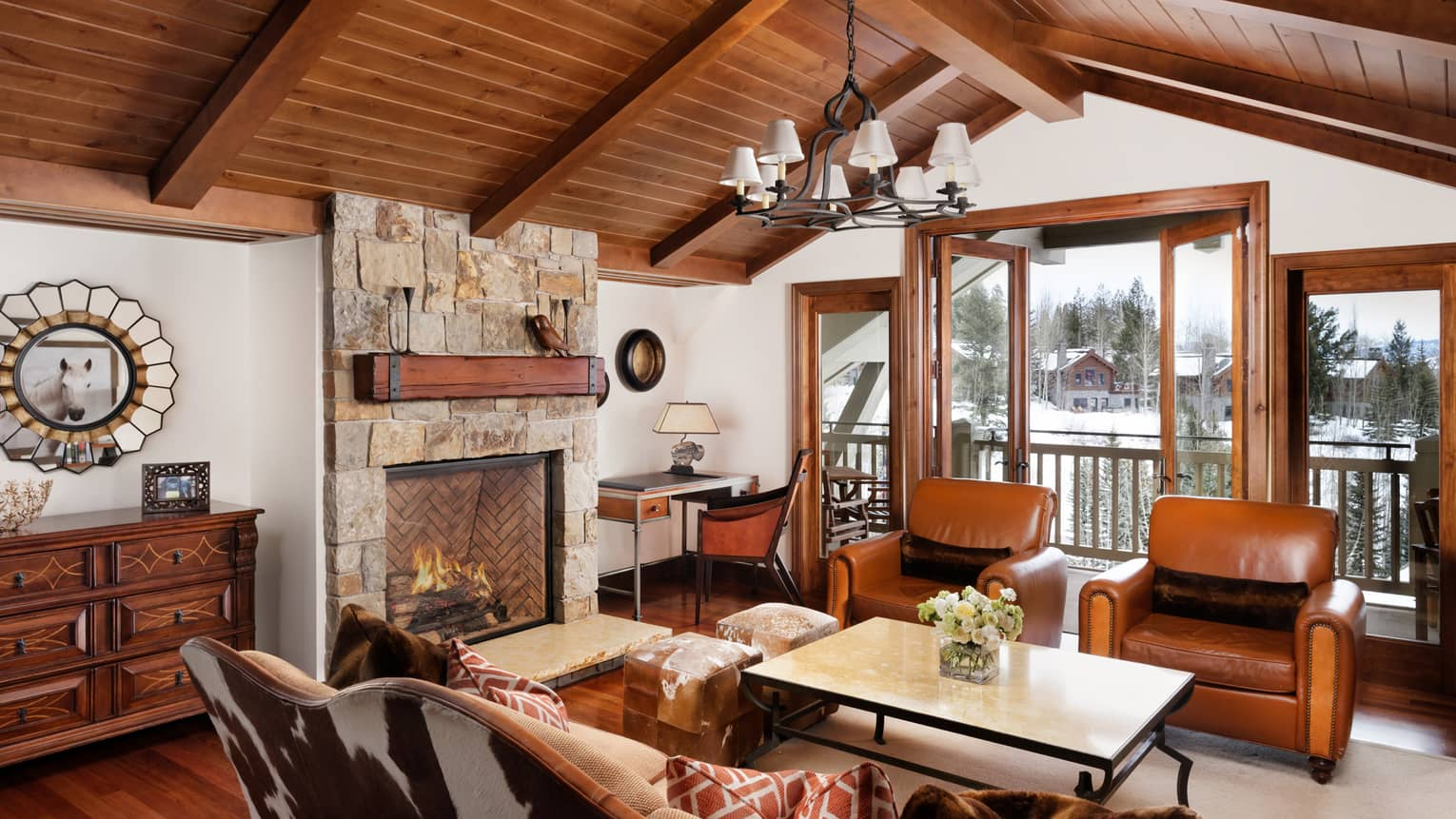 Cowhide sofa, leather armchairs. stone fireplace under arched wood beam ceiling