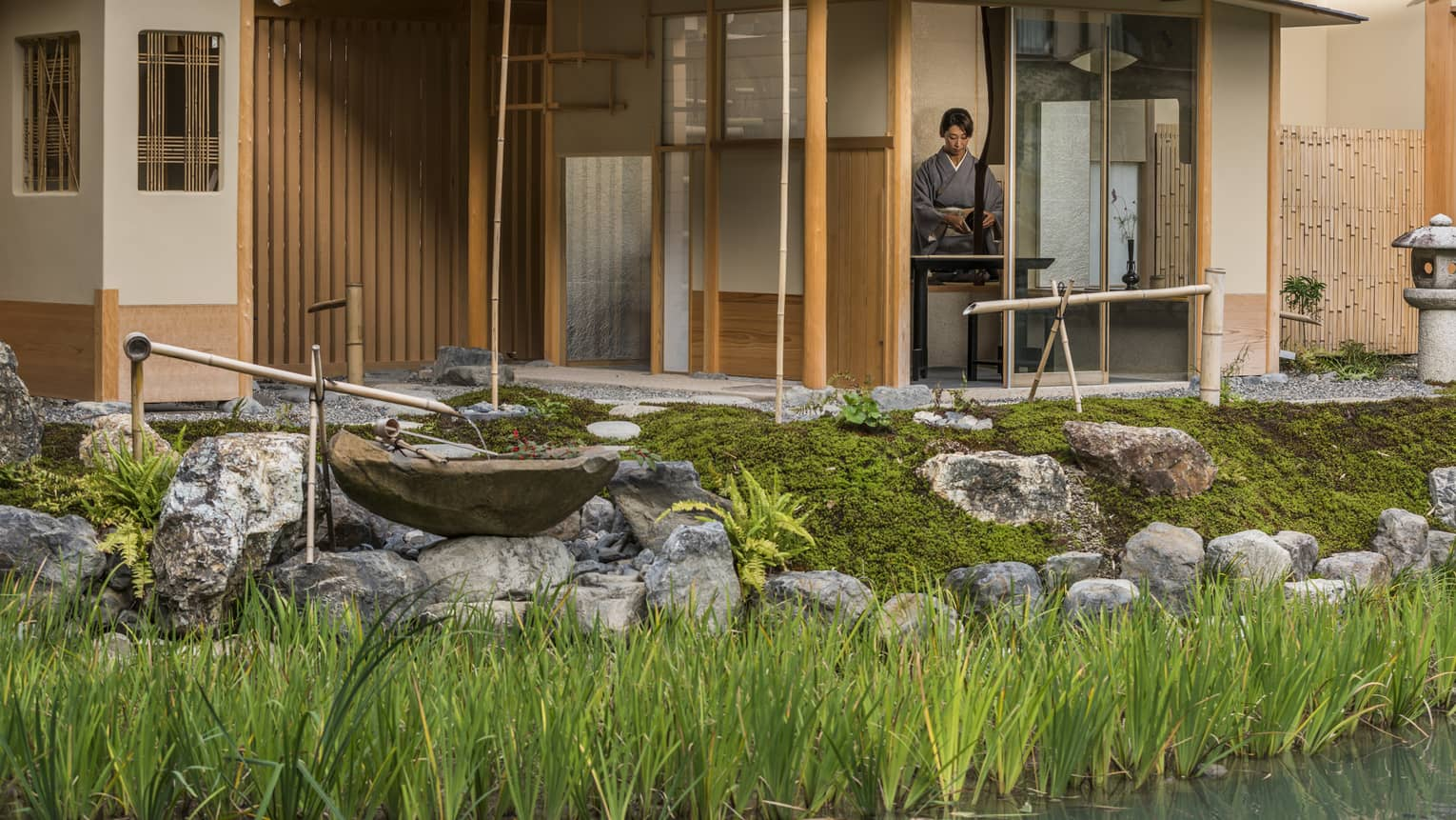 Rock garden, fountain in front of Shakusui tei building, woman in robe behind window