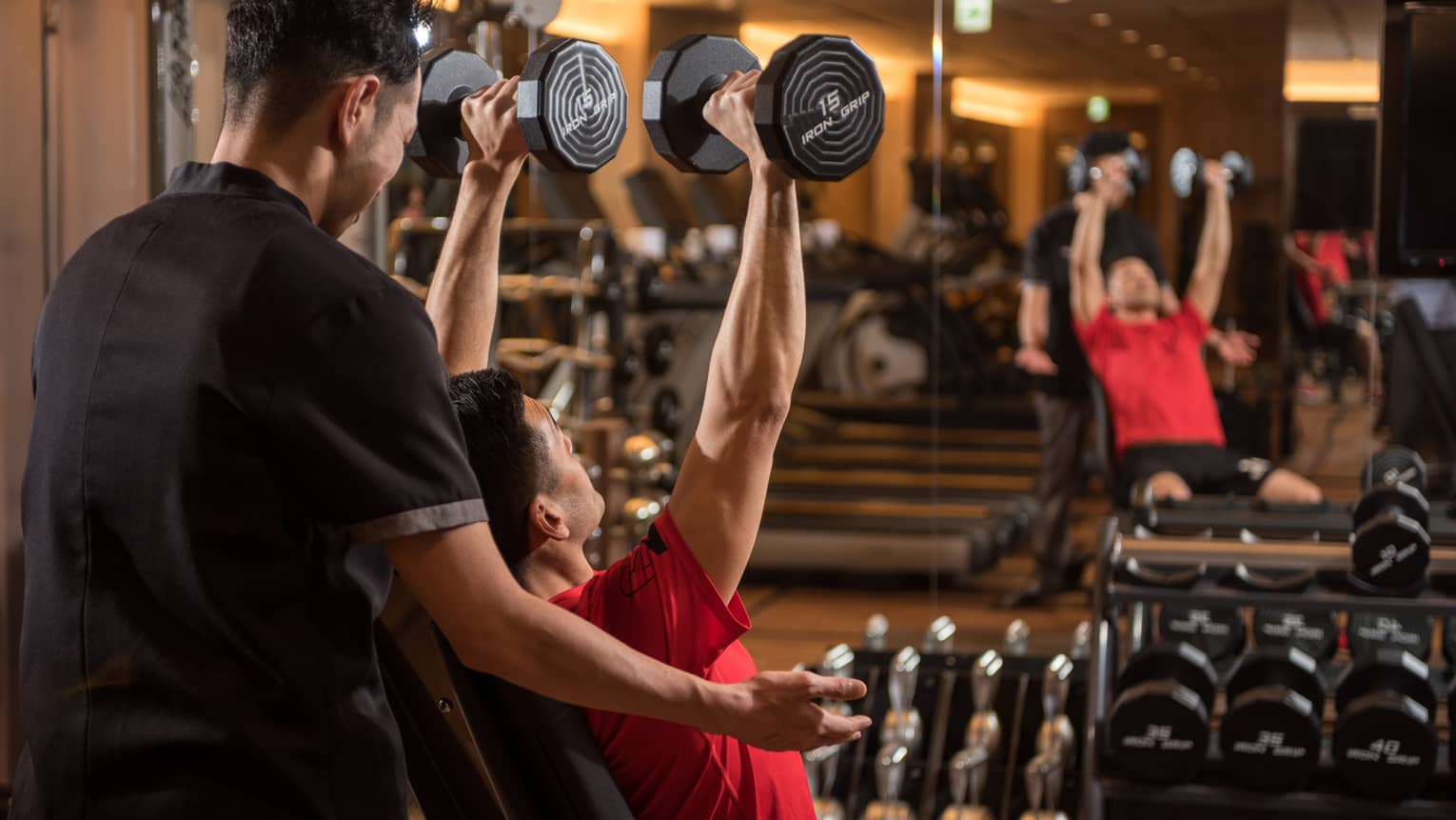 Man in chair in front of mirror lifts two 15 lb. weights above his head while personal trainer assists