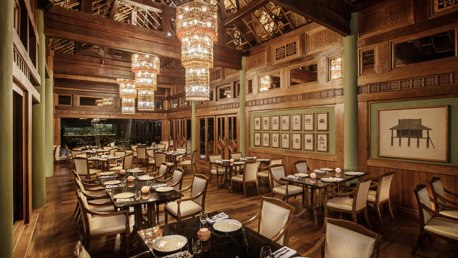 Long crystal chandeliers hang from high ceilings over KHAO indoor dining room with wood decor