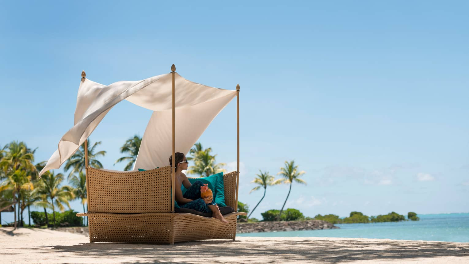Woman lounges on wicker cabana chair with flowing white curtains on beach
