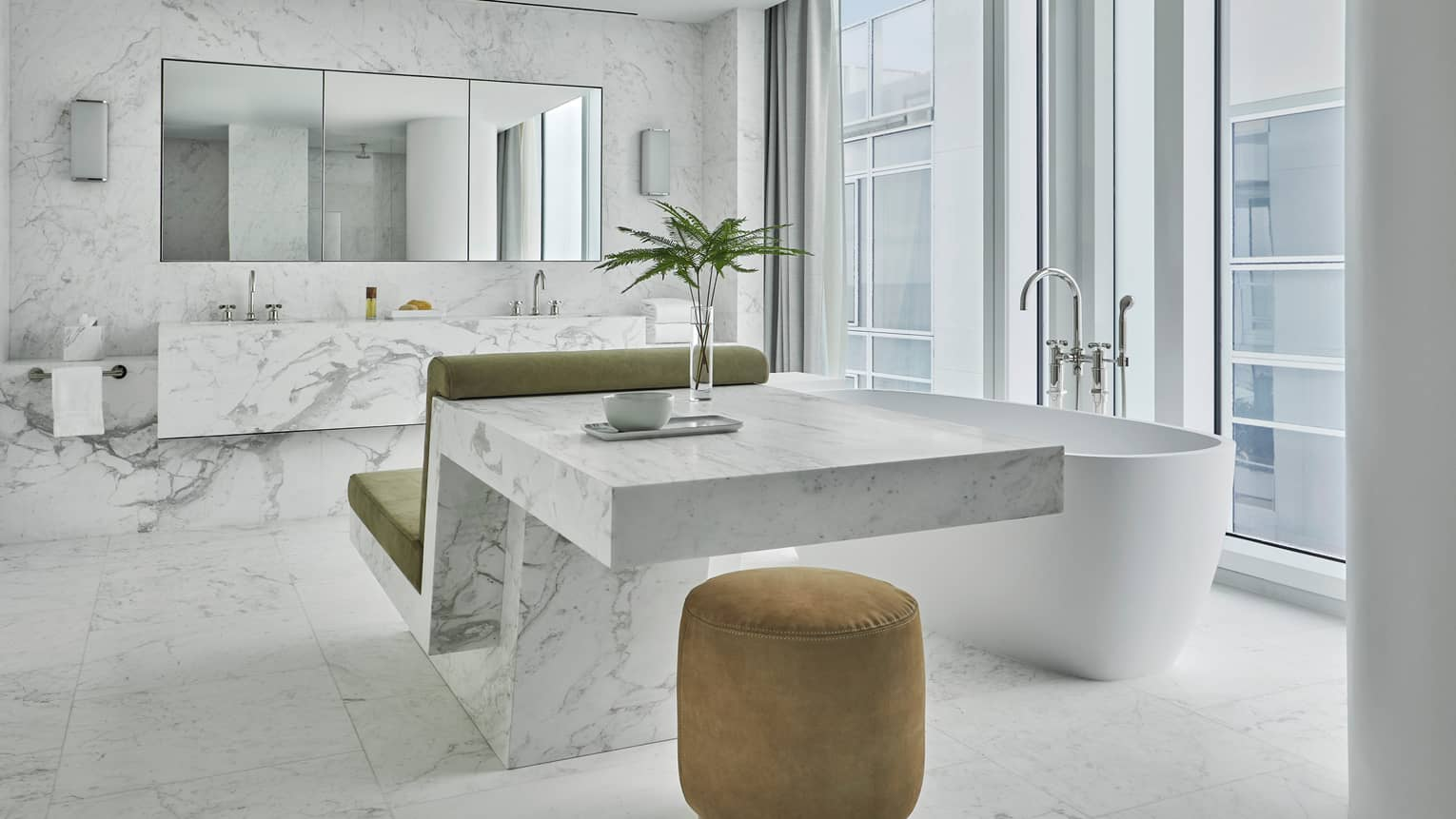 Large, modern white marble bathroom with vanity and sink, plush chair against counter, velvet bench