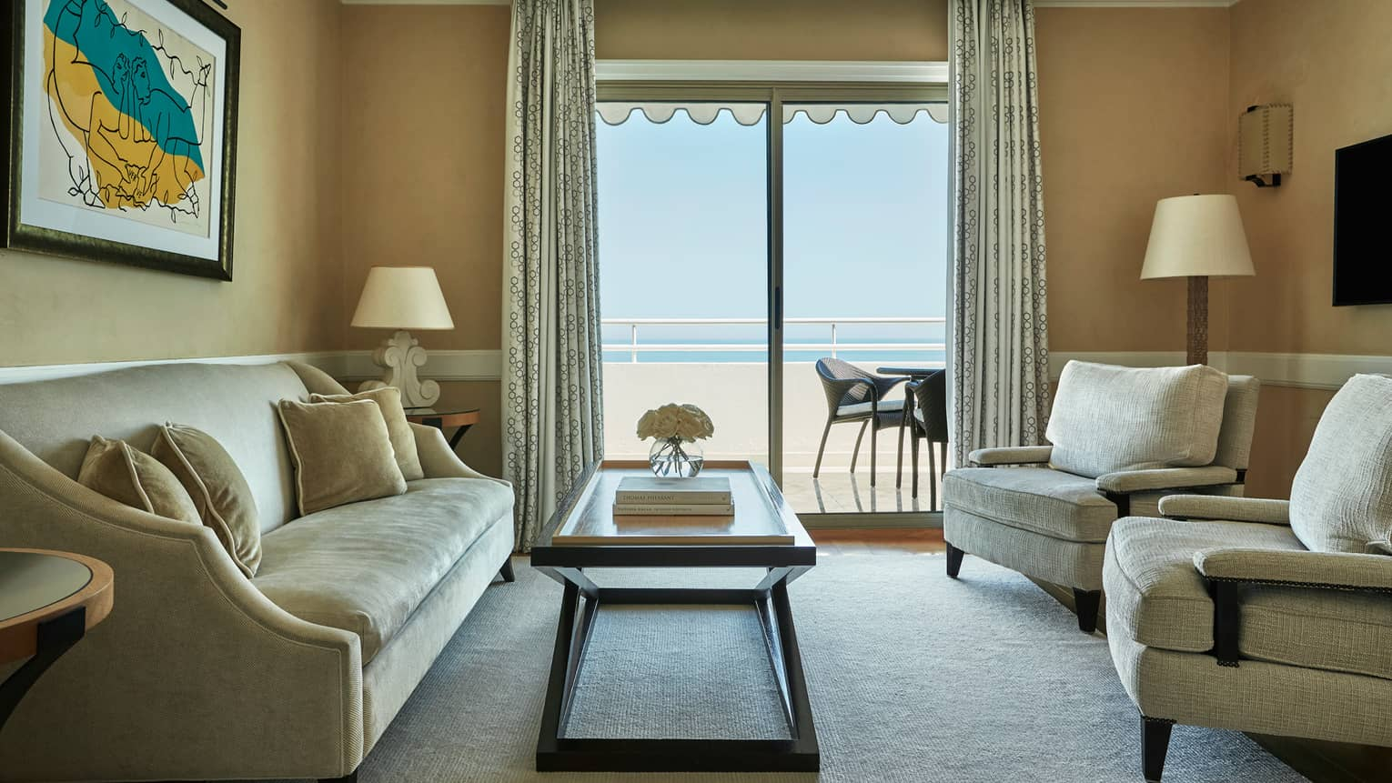 Rooftop Suite beige sofa, armchairs, table by glass sliding doors to balcony