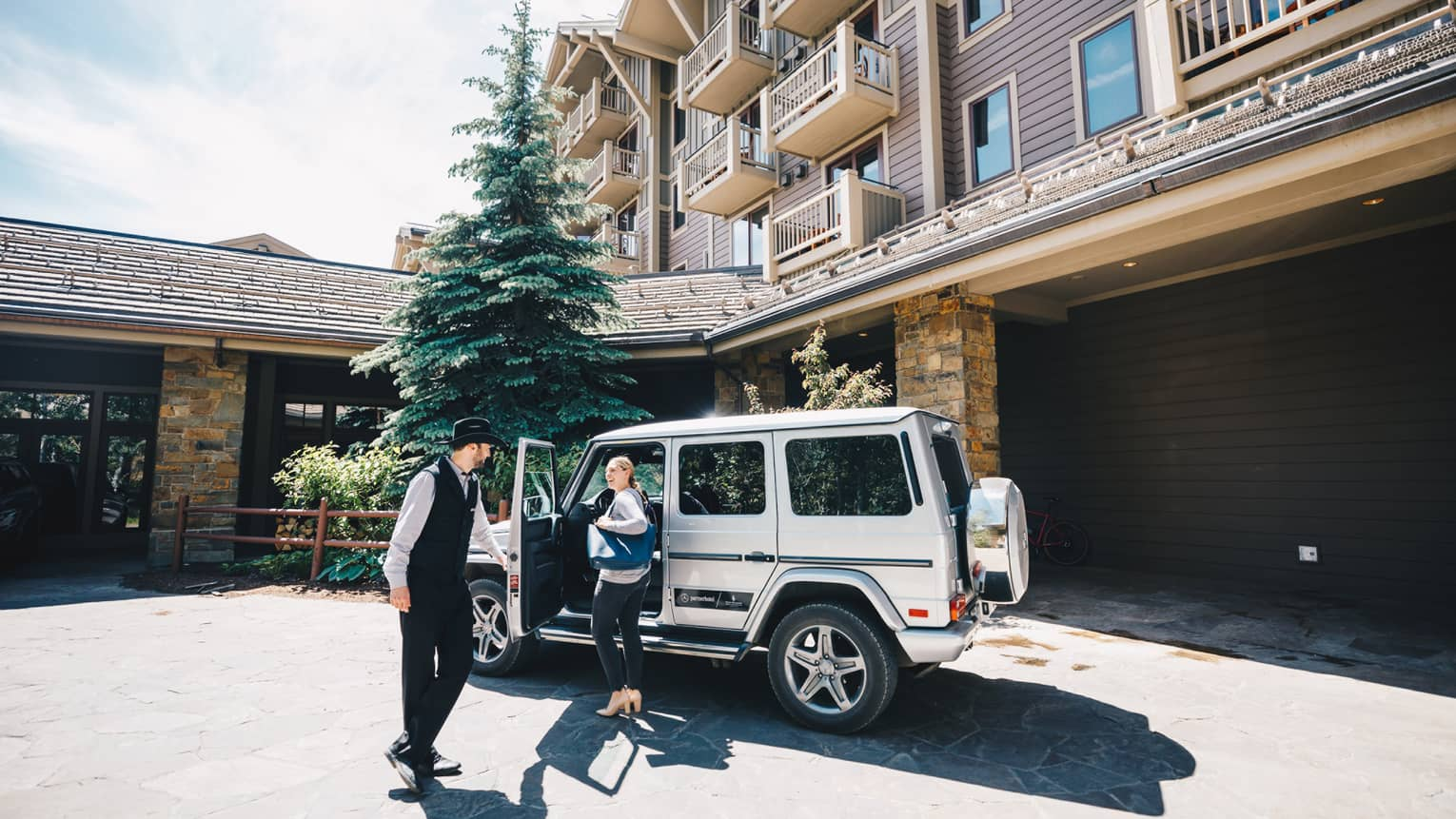 Resort staff opens the driver-side door of a luxury utility vehicle parked in the driveway for guest