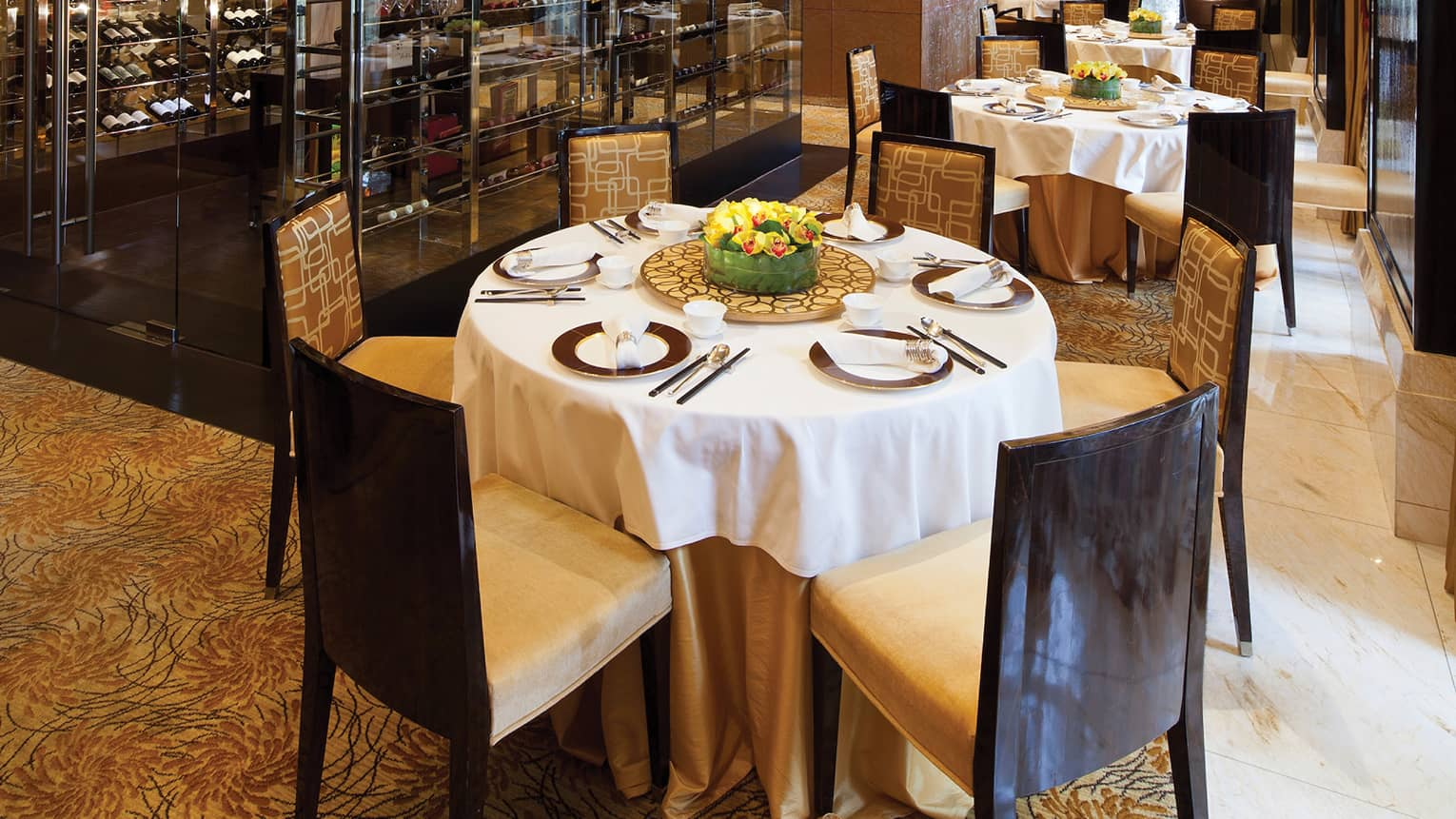 Round dining tables with white cloths, chairs in front of large wine cellar racks