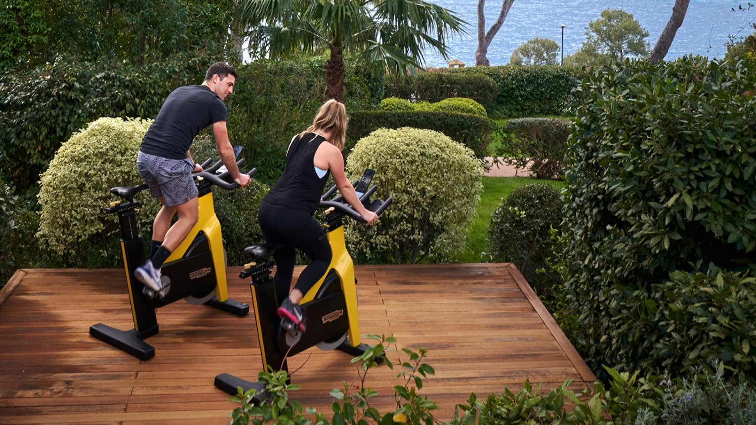 A man and a woman ride stationary bikes on outdoor wooden platform, sea in the distance