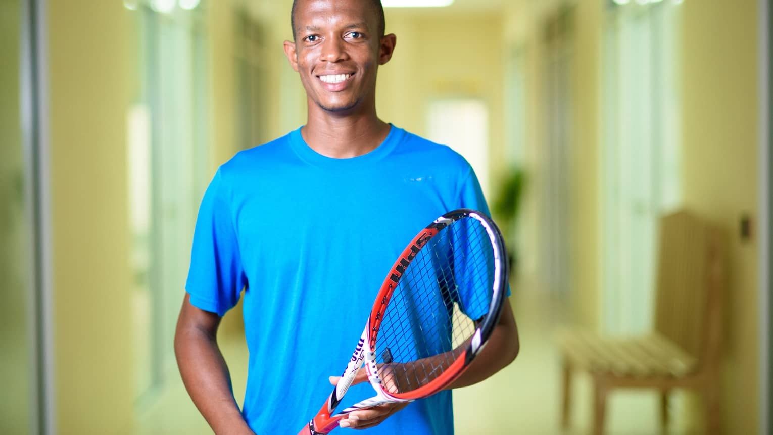 Smiling man in blue shirt holds red tennis racket
