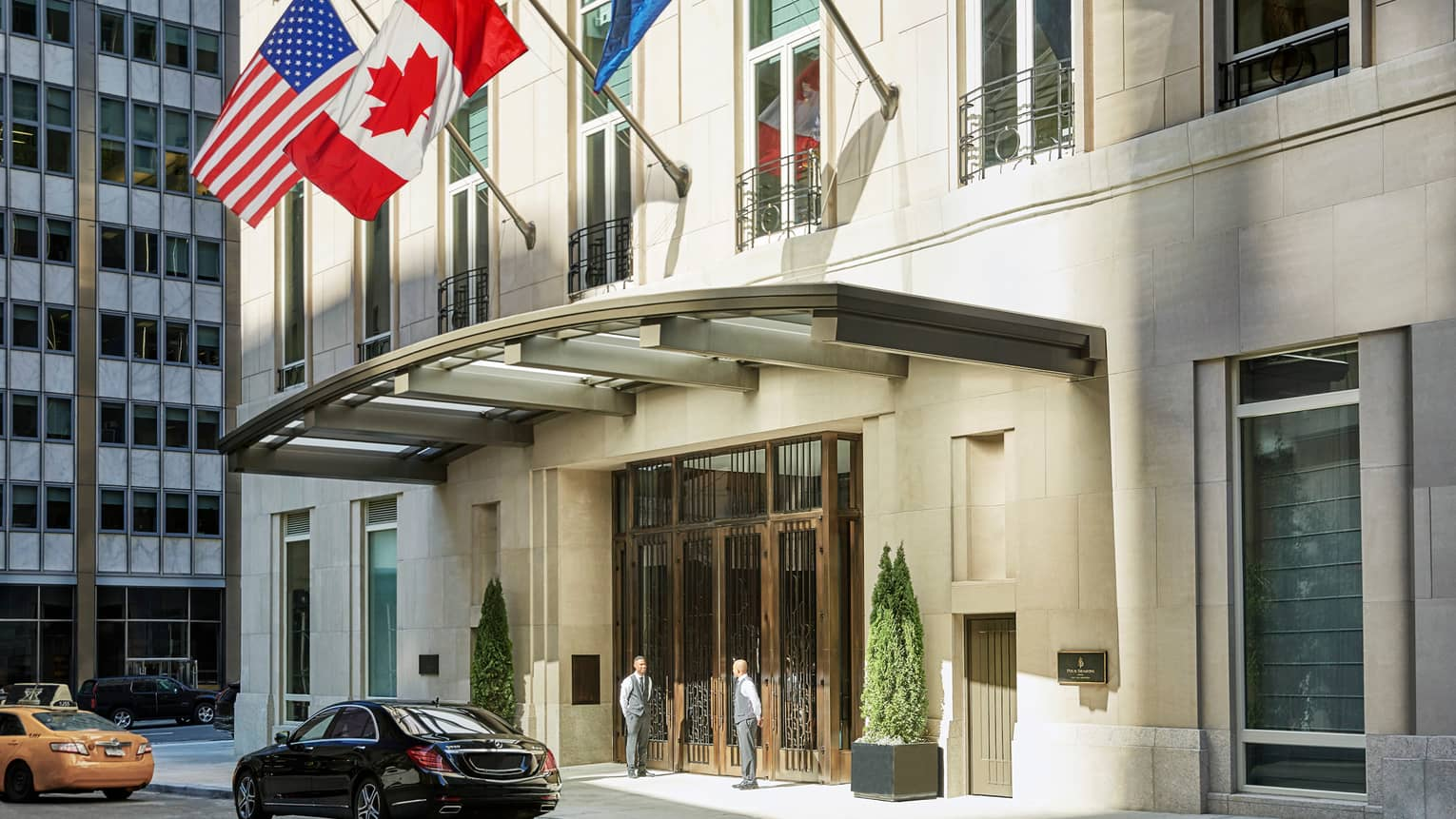 American and Canadian flags fly over Four Seasons Hotel New York Downtown entrance, door staff