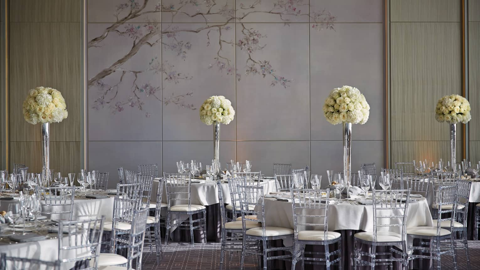 Vinci ballroom banquet dining tables with tall white flowers, accent wall