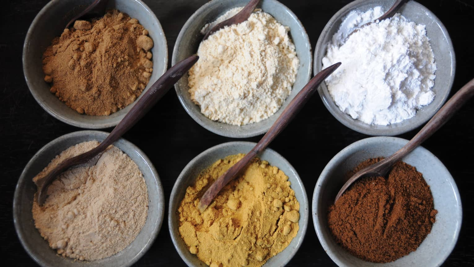 Aerial view of small spa bowls with powdered spices, clays, wood spoons
