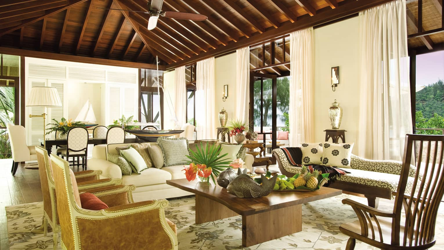 Three-bedroom Beach Suite bright living room with white sofas and elegant chairs, wood beam roof
