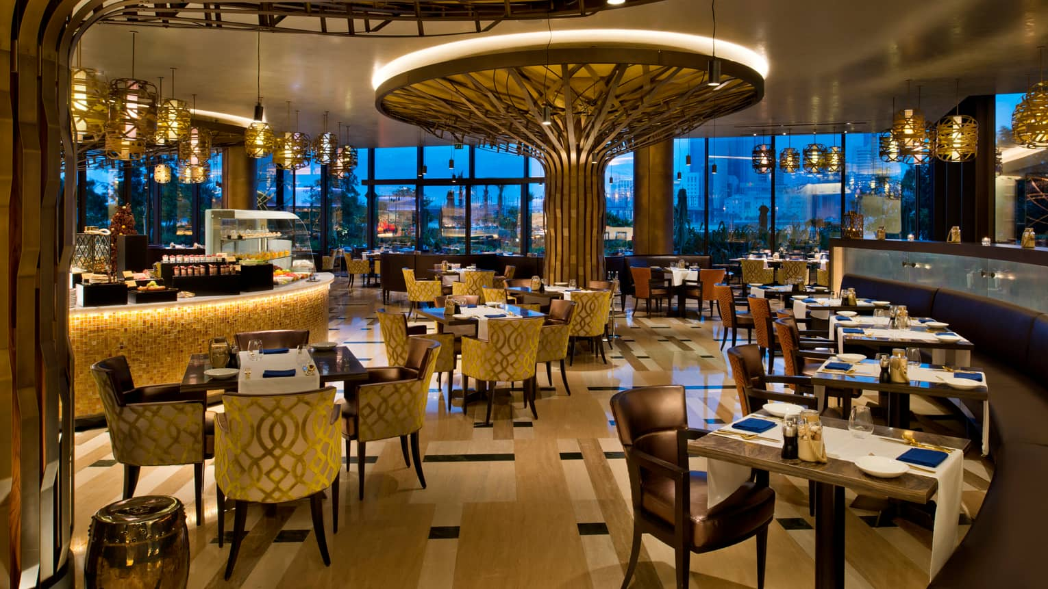 Bahrain Bay Kitchen dimly-lit dining room with gold velvet armchairs, tile bar, tall tree-shaped wood sculpture with light