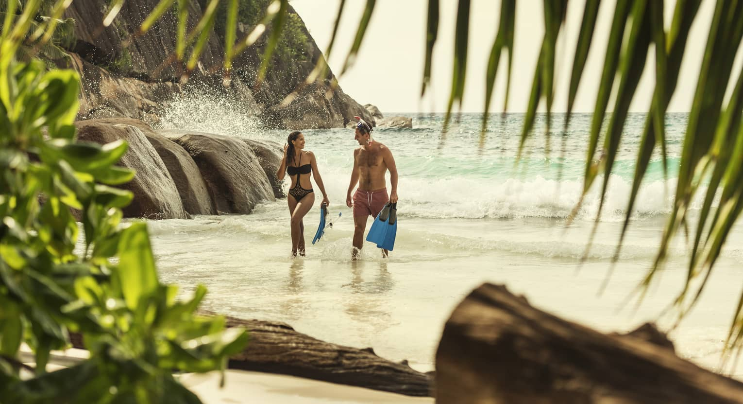 Man and woman in swimsuits hold snorkelling fins, walk from the ocean to beach